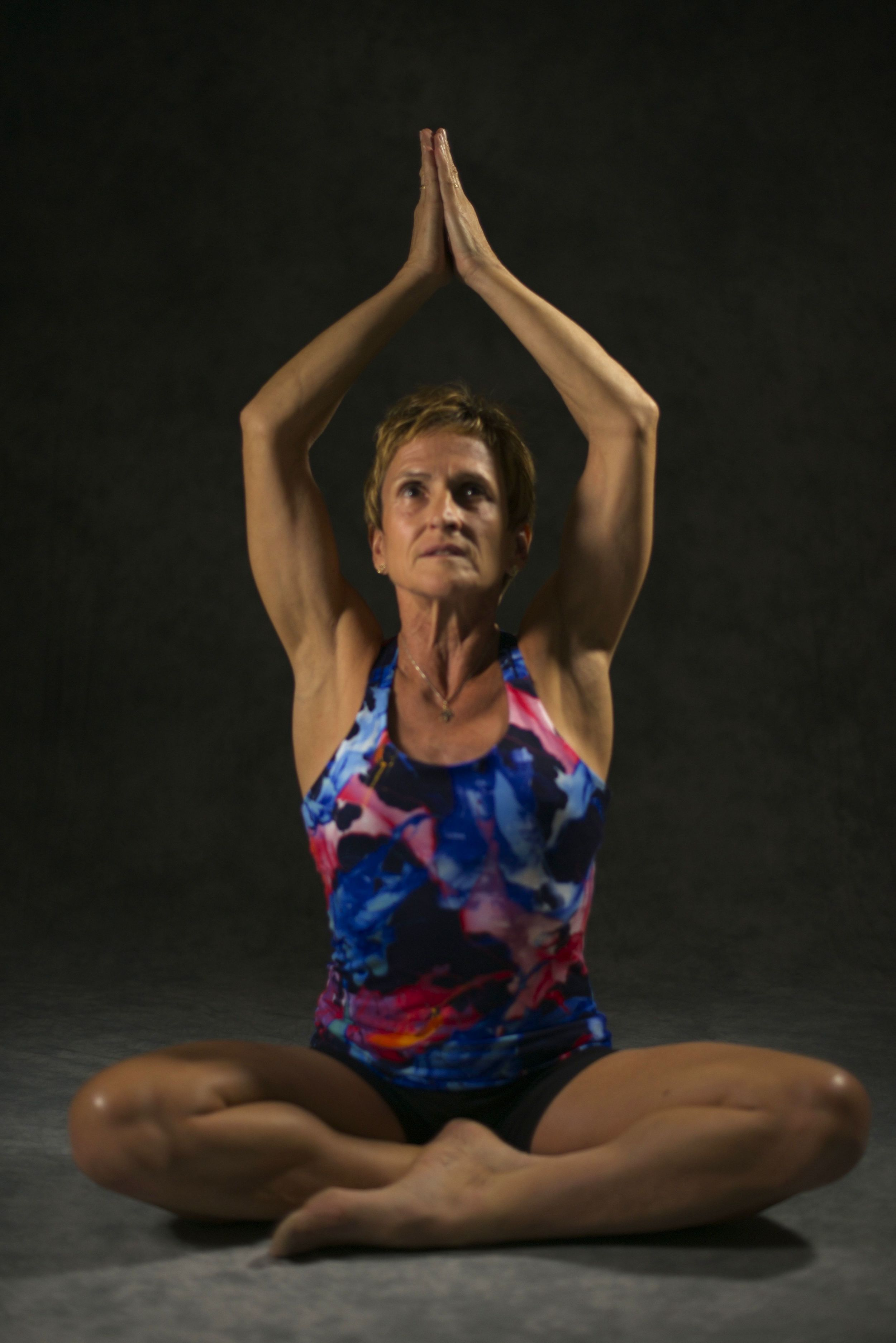 Val in seated posture with prayer overhead