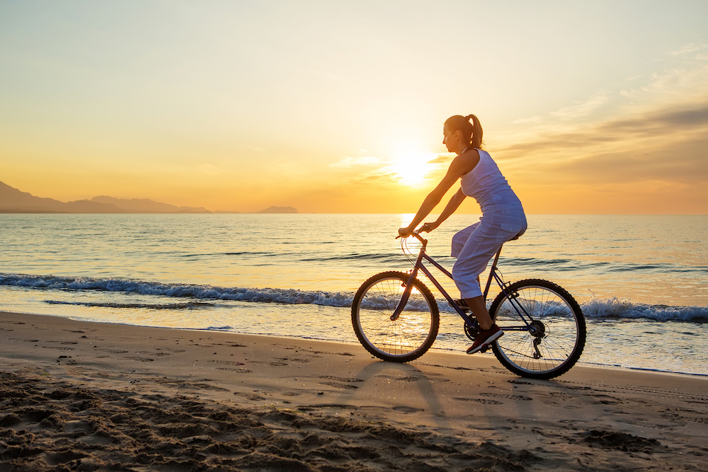 bigstock-Woman-On-Vacation-Biking-At-Be-145689152.jpg