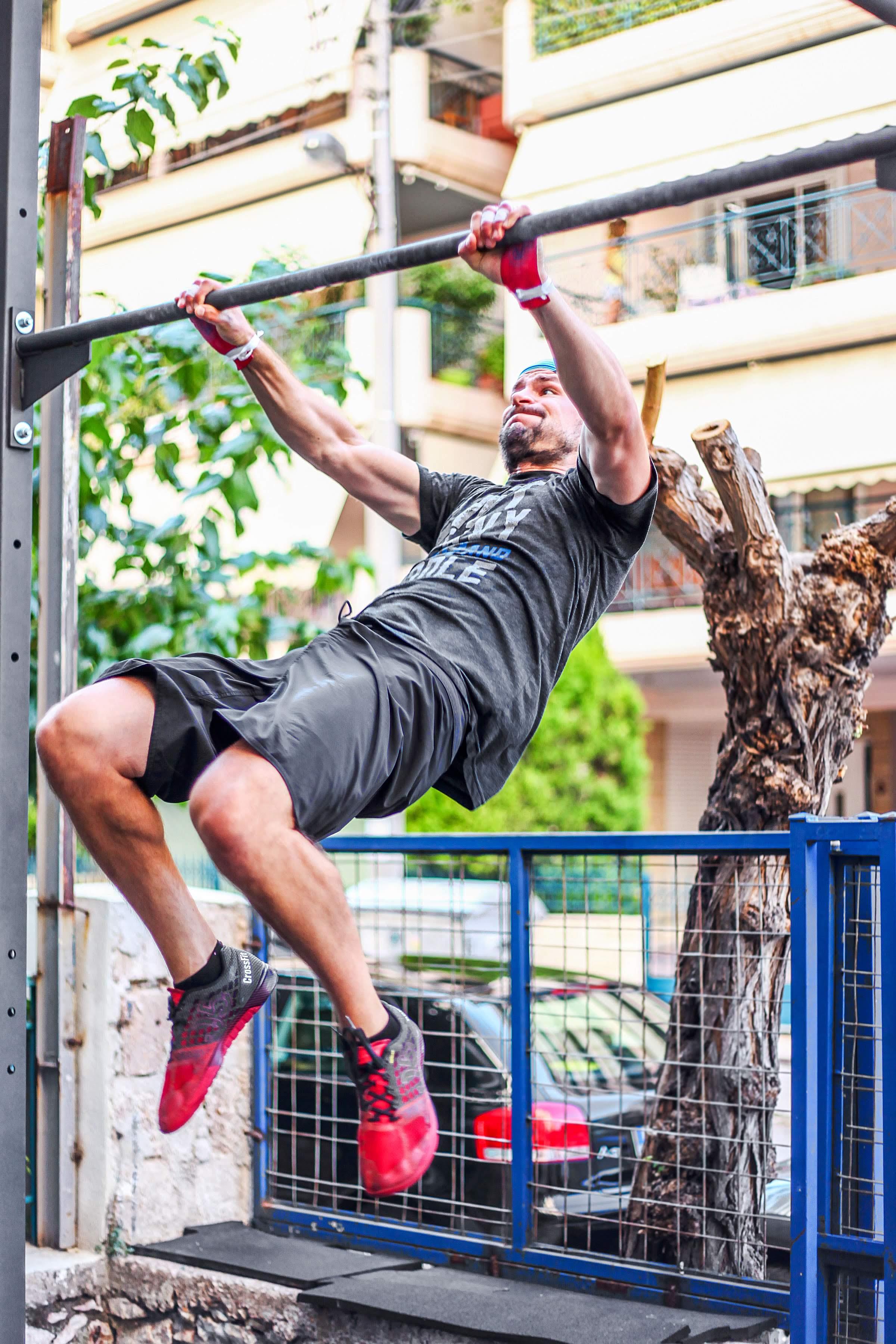 Tony Beringer mid-bar muscle-up at CrossFit Piraeus in Greece.