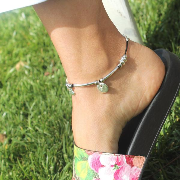 The  Gigi Anklet  is adorned with hammered disc, heart and dangle charm.