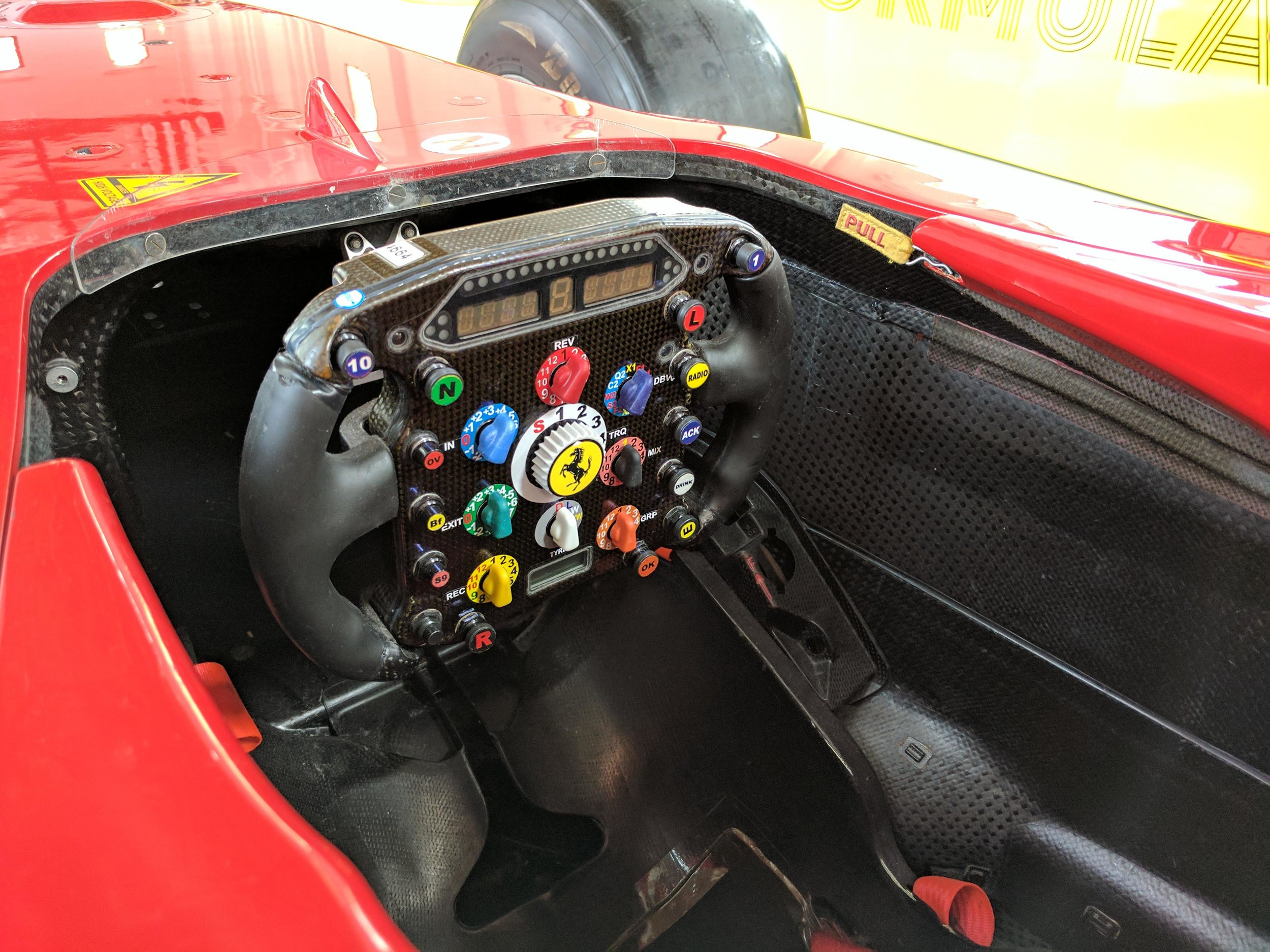 An old style steering wheel. Not as complicated as the ones today.      And a pit board for the current team.
