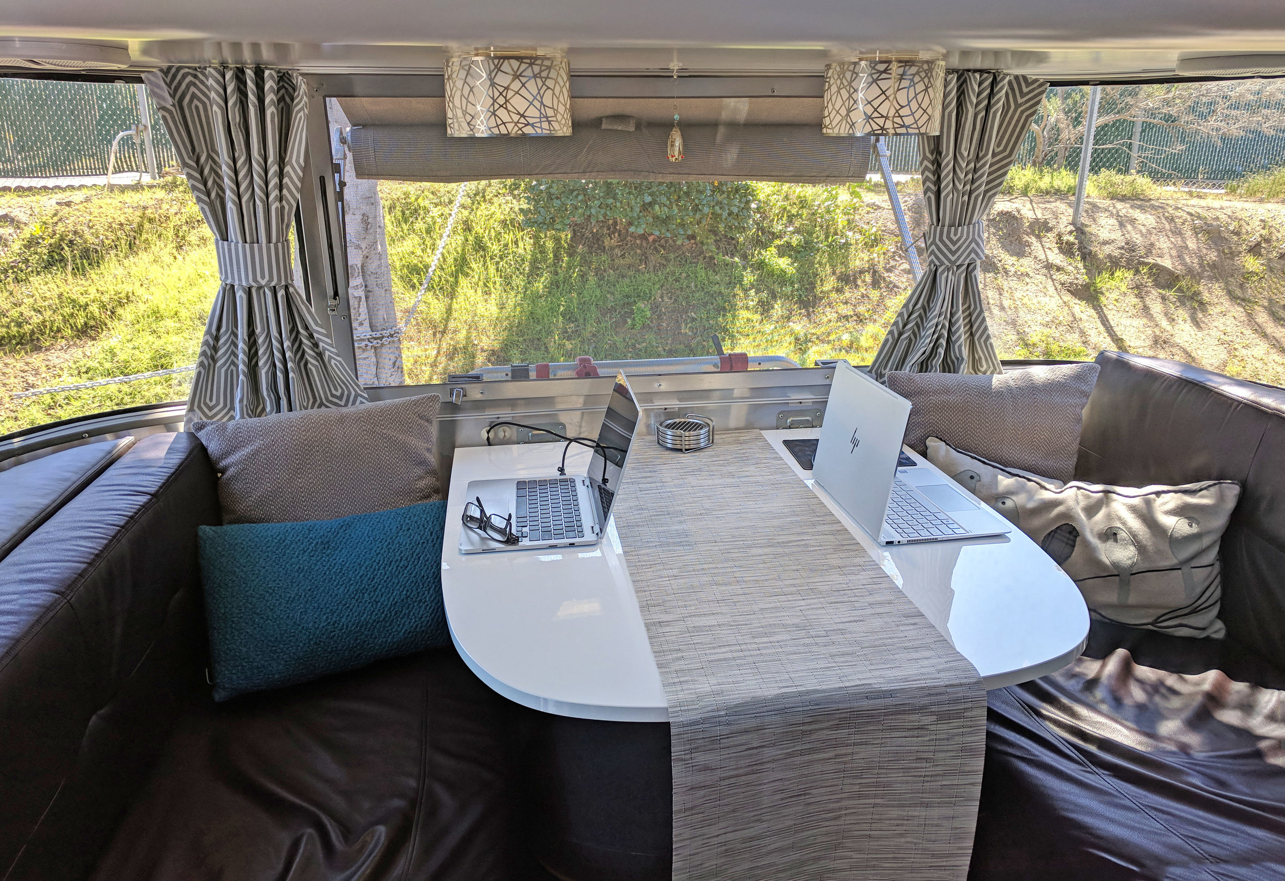This is where we spend most of our time in the trailer. Working, eating and relaxing. We changed these curtains out too, and replaced the table top with a bright white one.