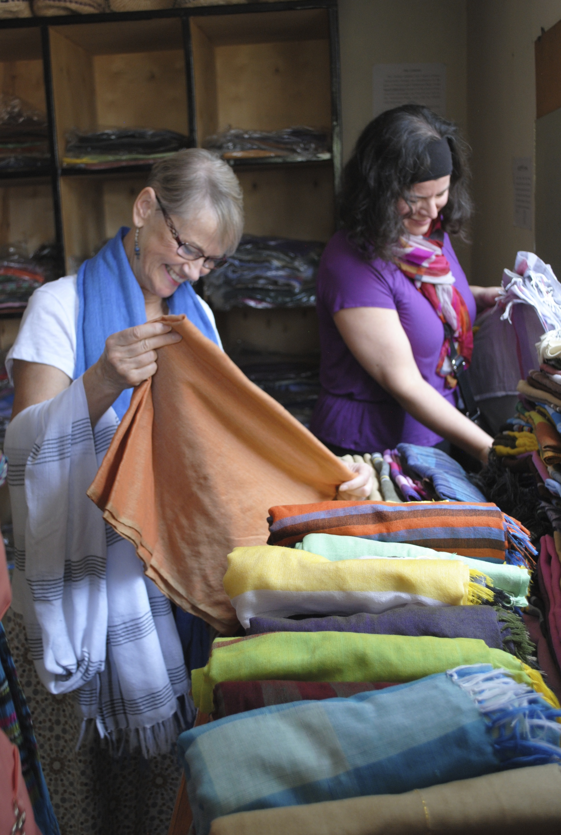 Val Easton and Shelley Green look through scarves made at the Former Women Fuel and Wood Carriers Association. That group offers alternative employment to women who used to work carrying massive loads of wood on their backs, up and down the hills of Addis Ababa.