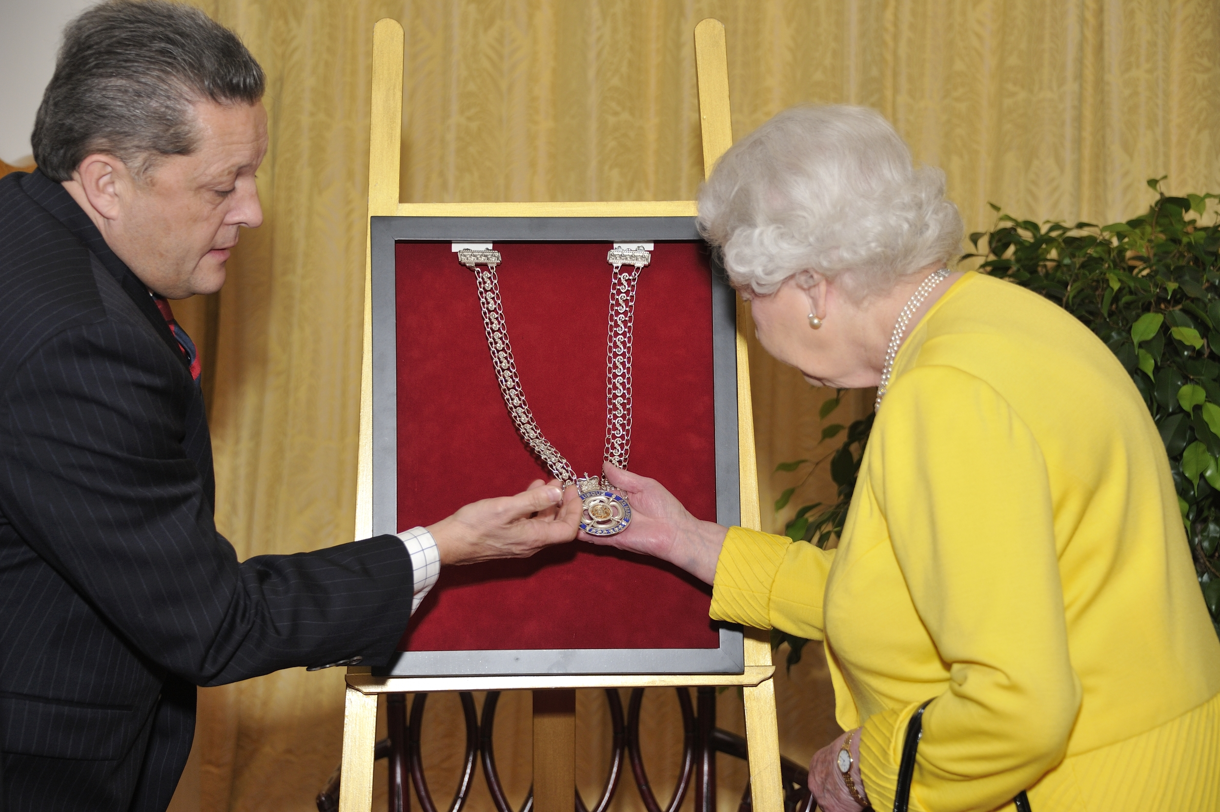 Queen Elizabeth II picking up the chain of office