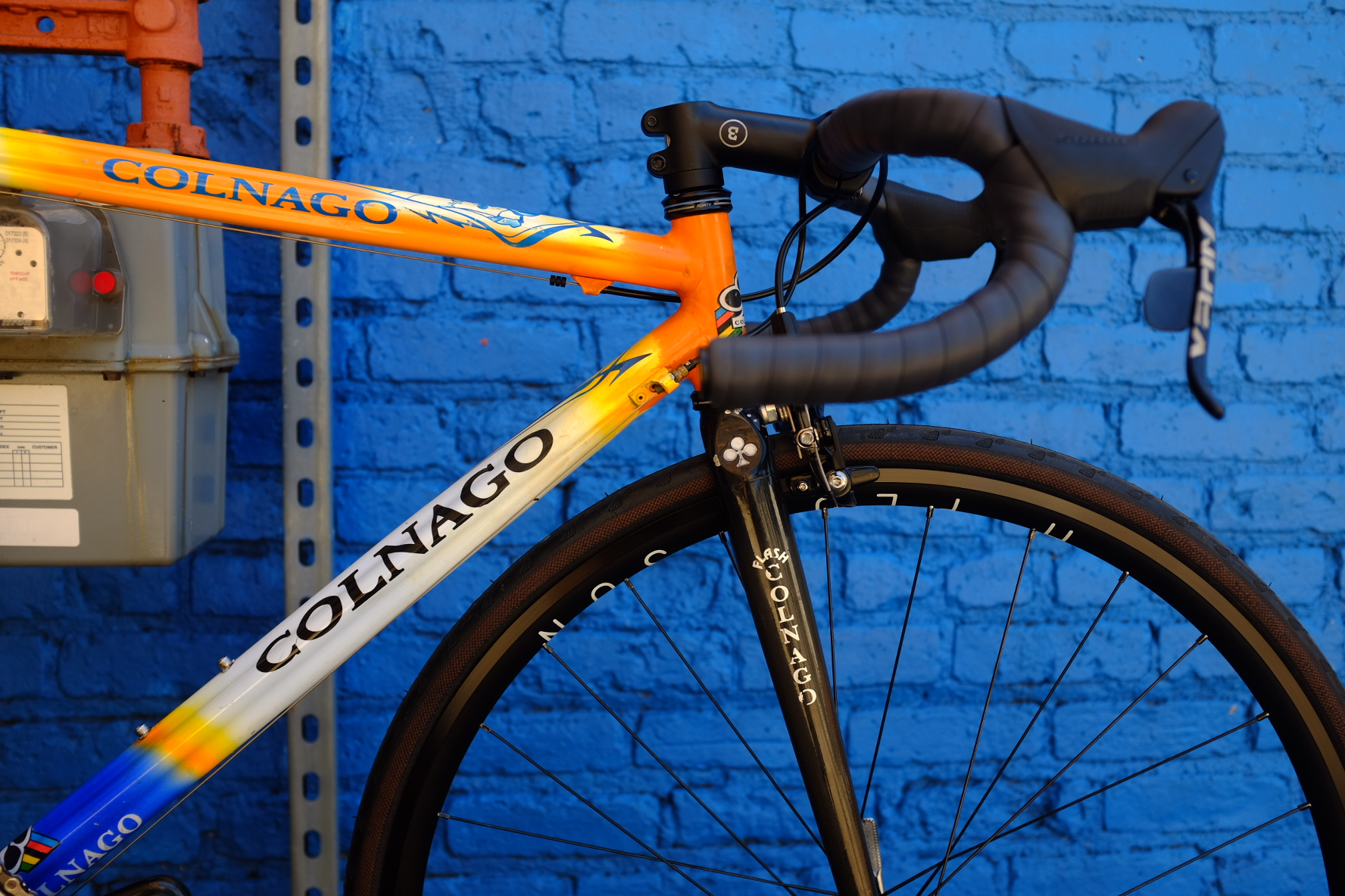 Closeup of an orange and blue Colnago custom build.