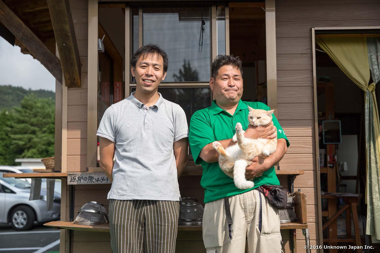 マネージャーの日隈稔幸さんと、ネコのシロちゃんと受付の前で撮影