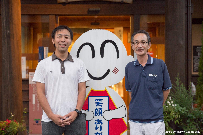 支配人代理の小路敏弘さん、マスコットキャラクターのどんタロくんと入口の前で撮影