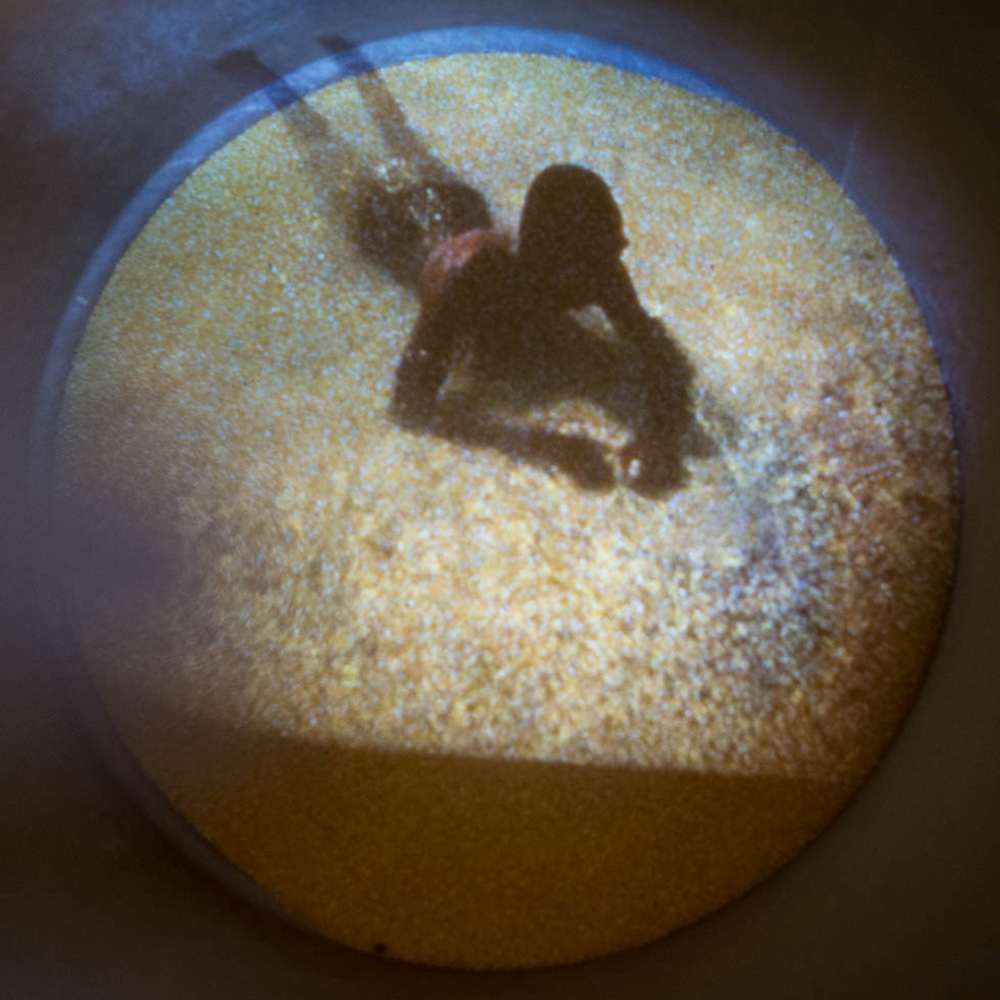 Stills of Video Projection on Cornmeal inside shipping barrel. Duration 1:42