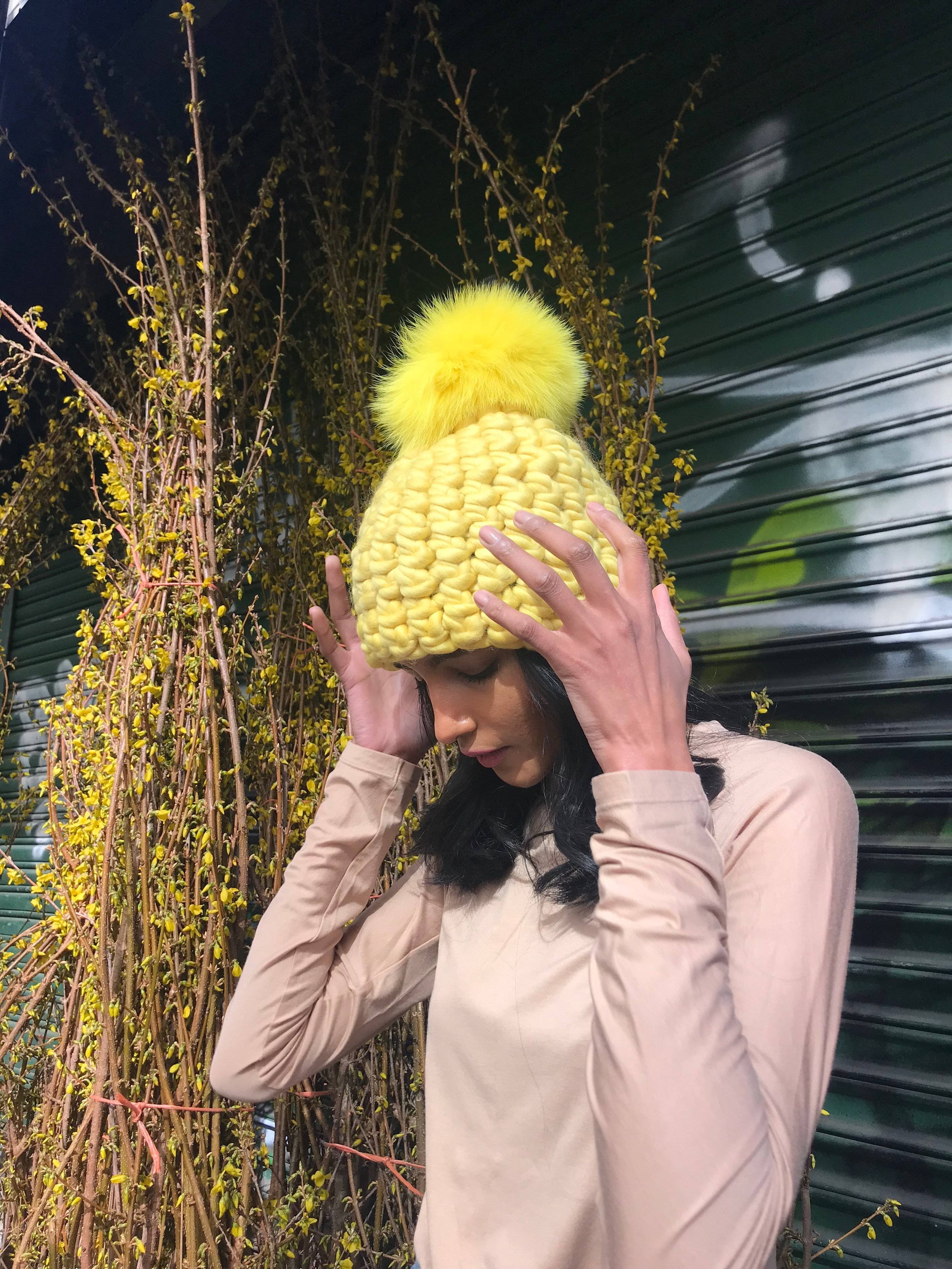shaanti is wearing  the yellow beanie pomster with yellow pom