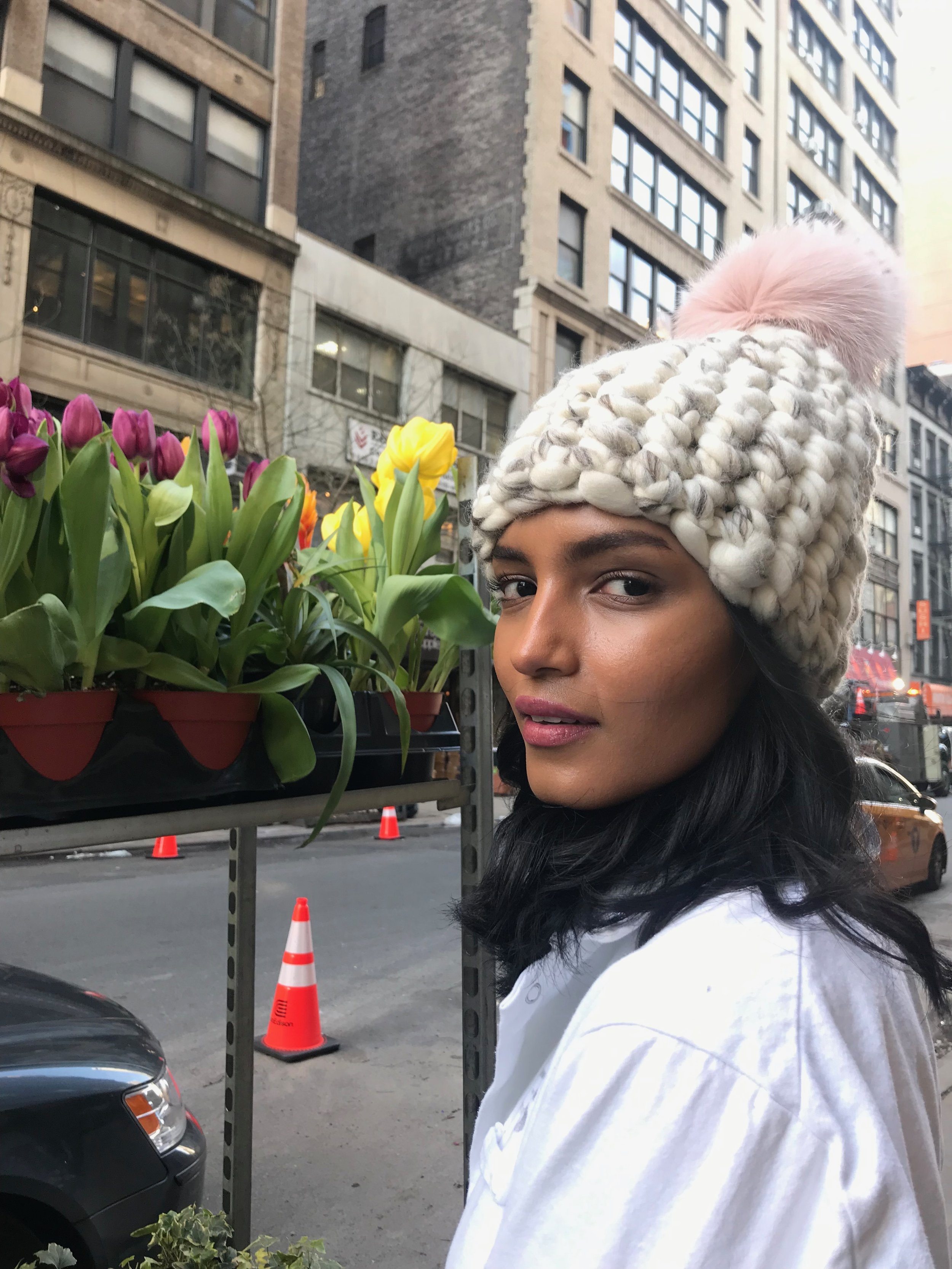 shaanti is wearing  the white/marble blend beanie pomster with pink pom