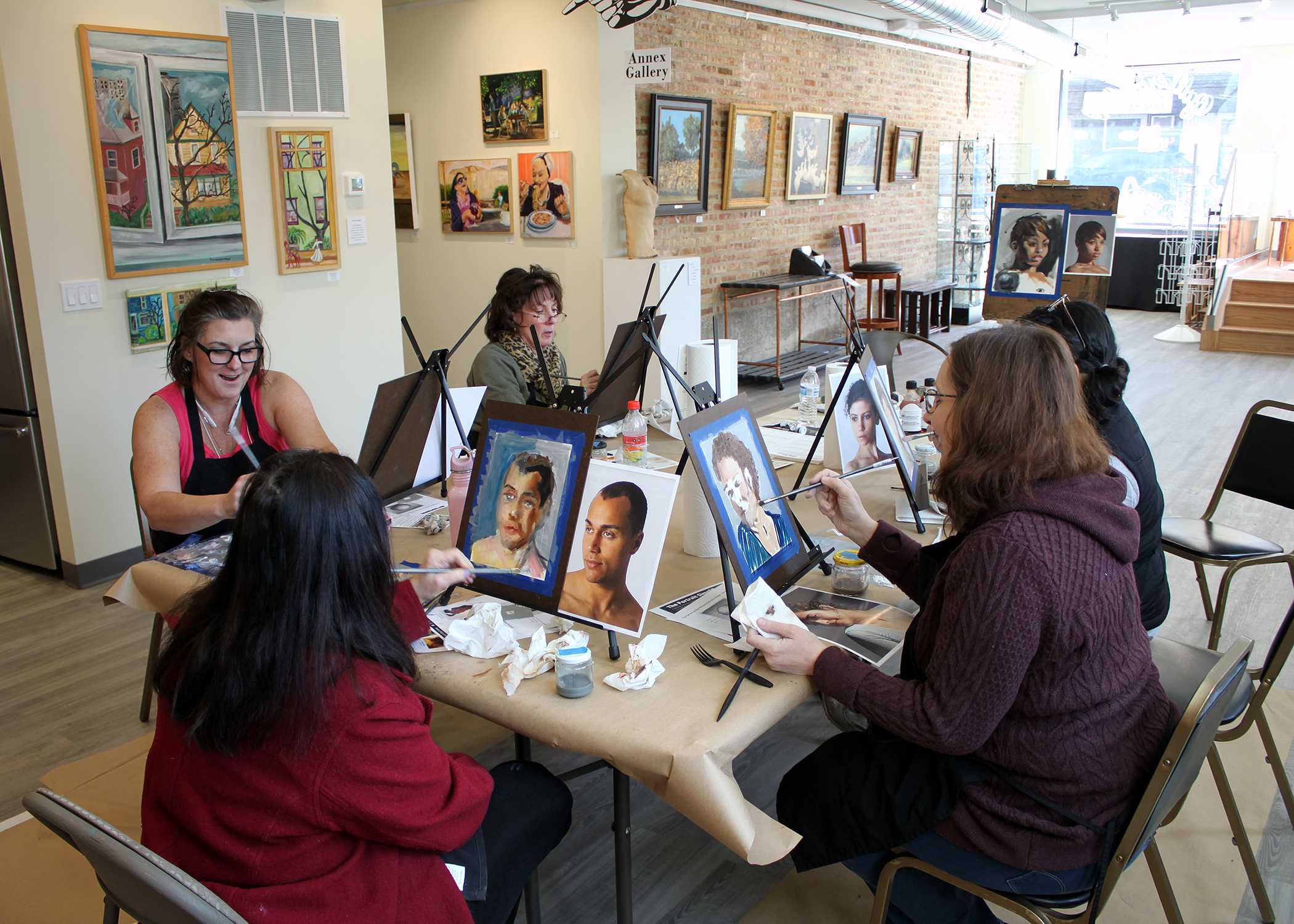 Students painting and experimenting with impressionistic portrait techniques at Gallery1070.
