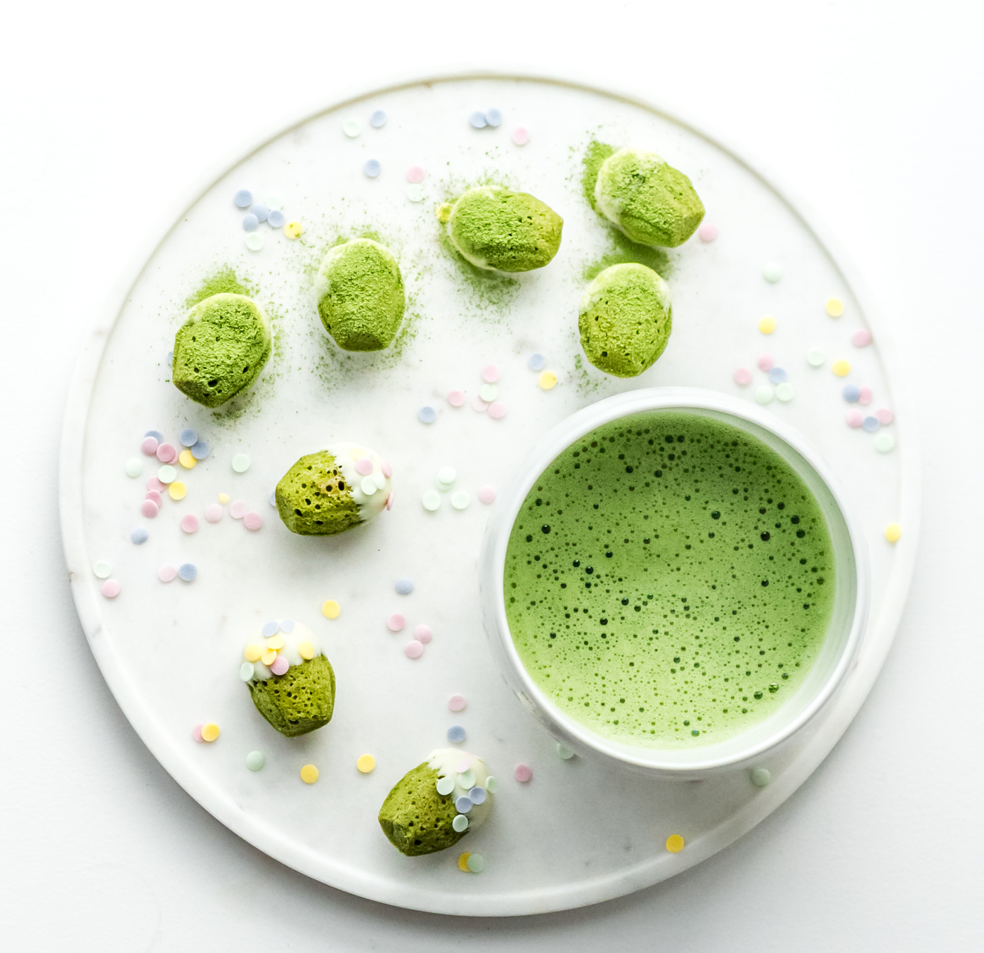 Matcha green tea mini madeleines with white chocolate and a bowl of matcha