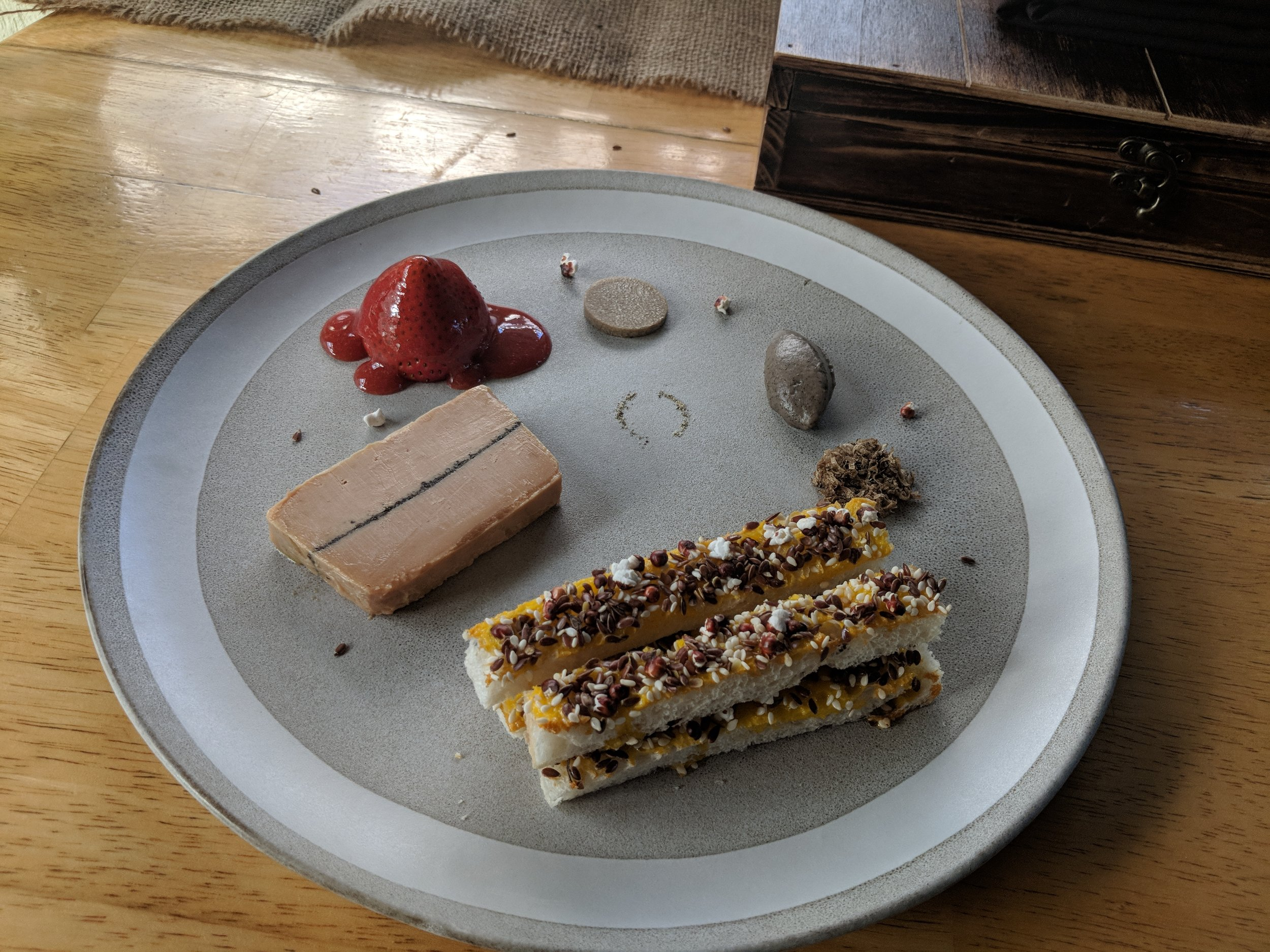 Terrine of foie gras with black pepper, summer truffle, and strawberry.