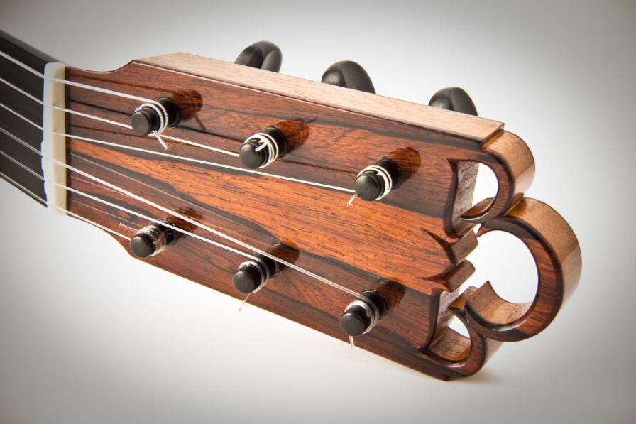 A striking headstock design featuring a fully carved relief with flamenco-style tuning pegs.