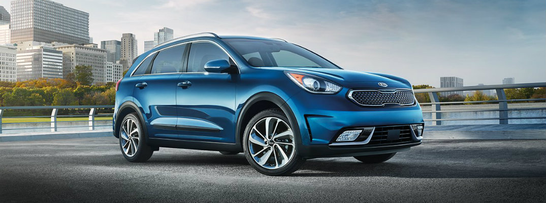 2019-Kia-Niro-exterior-shot-with-light-blue-color-paint-job-parked-on-a-gravel-plateau-near-a-lake-forest-and-city-of-skyscrapers_o.jpg