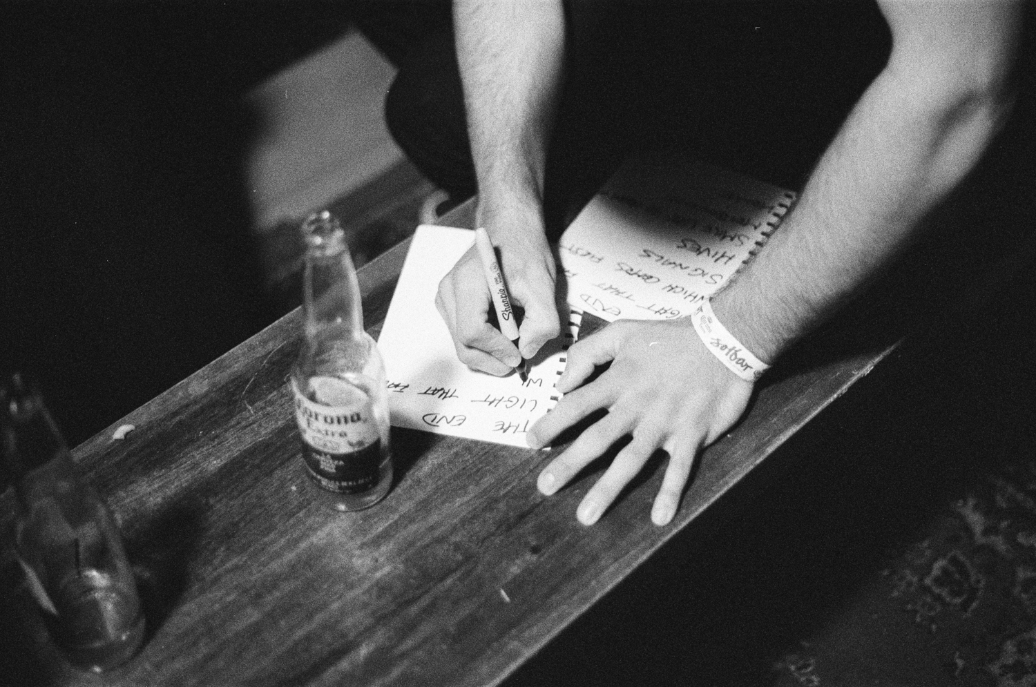 black and white, writing out set list with a corona