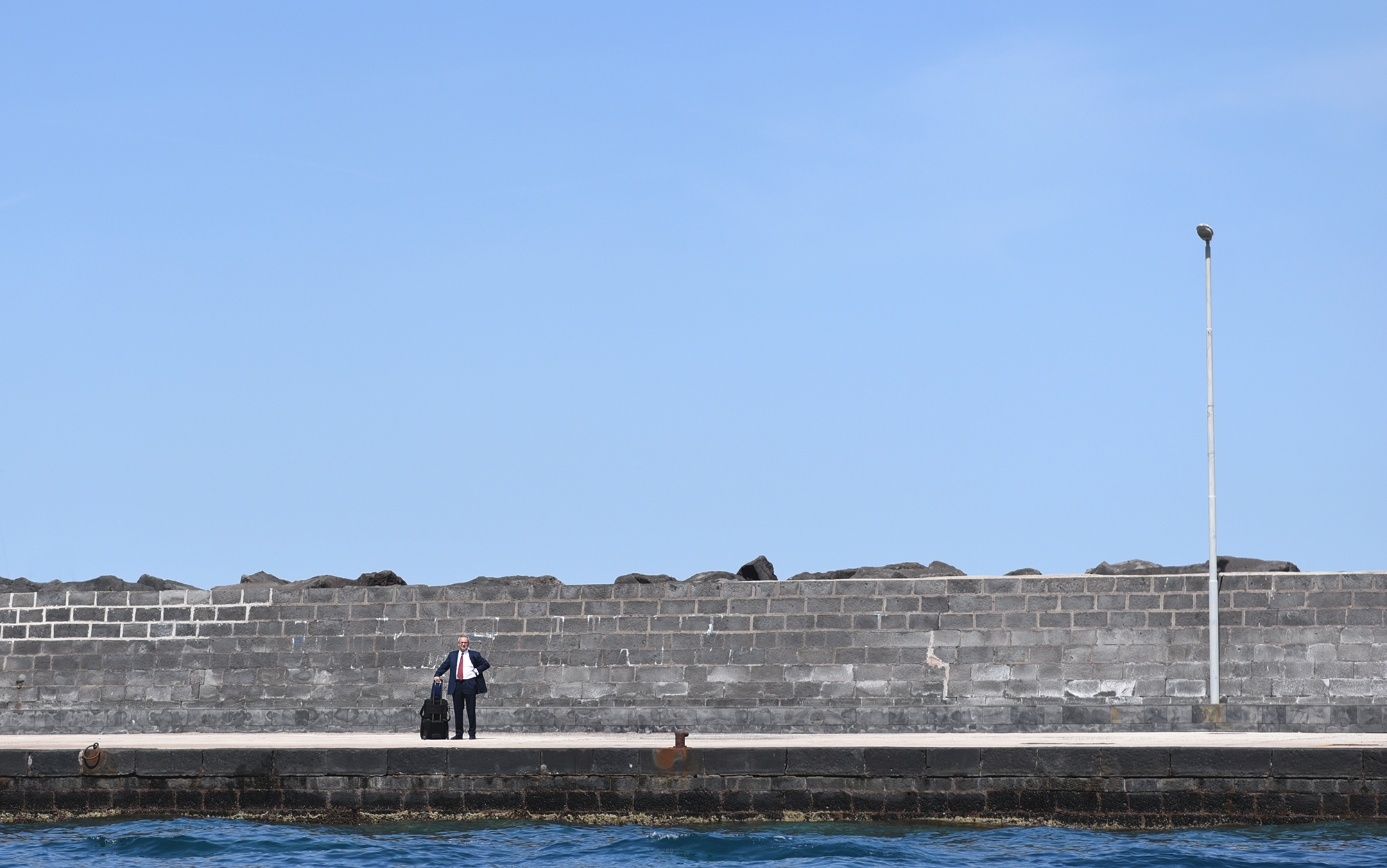A man waits patiently for a ferry in Capri, Italy. Photographed in April 2016.