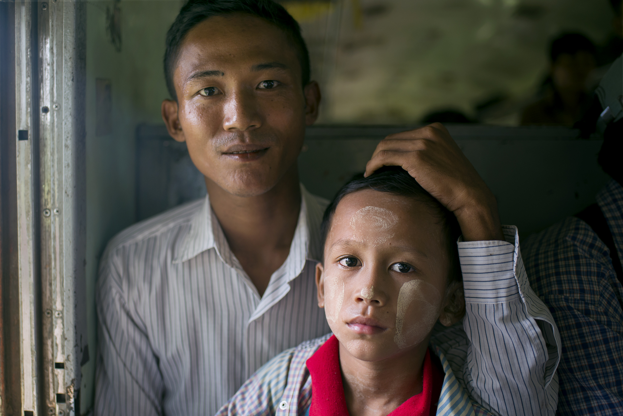 Father and son on the way to visit family in Mandalay. He is in the army and is based near Yangon, and uses the train to visit his family every week.