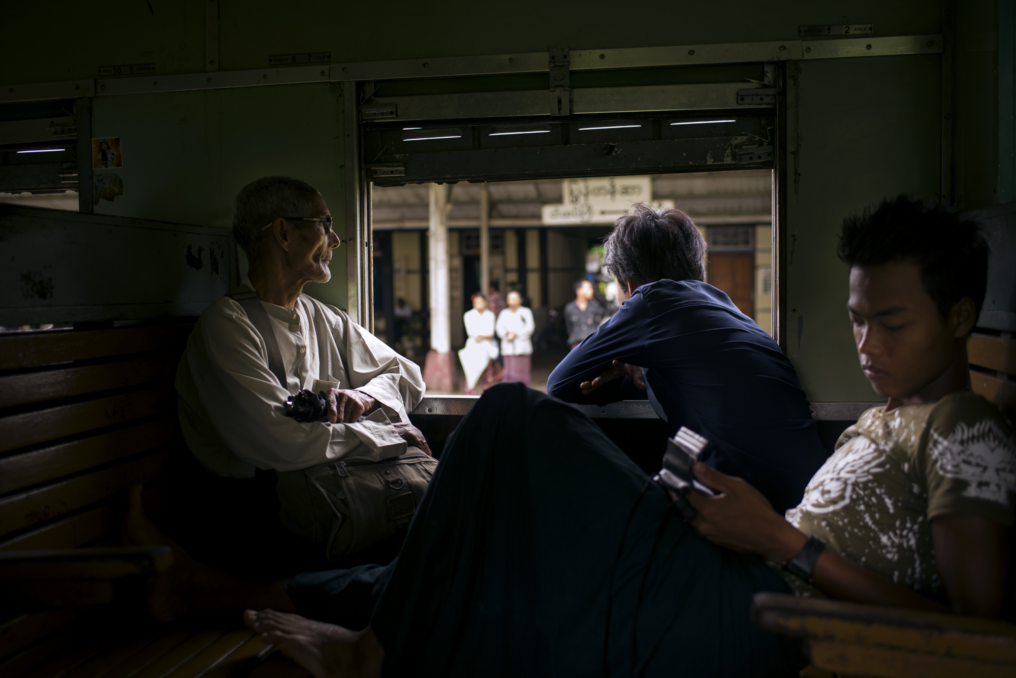 A family gets comfortable as the train departs Yangon on an the 18 hour journey up the country to Mandalay