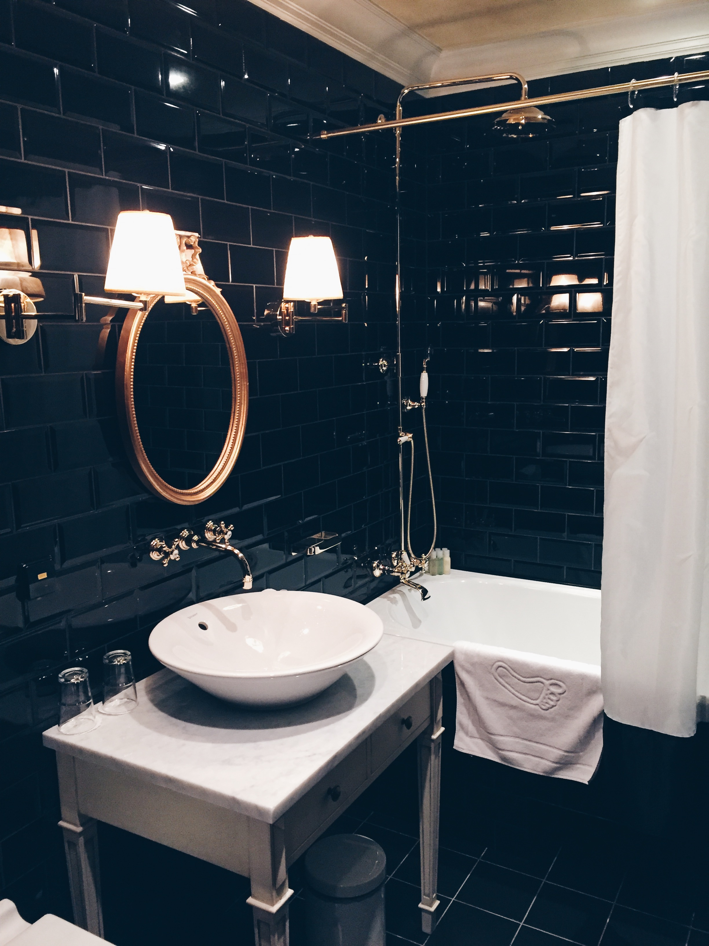 Bathroom inspo: floor to ceiling black subway tile with brass accents (swoon).