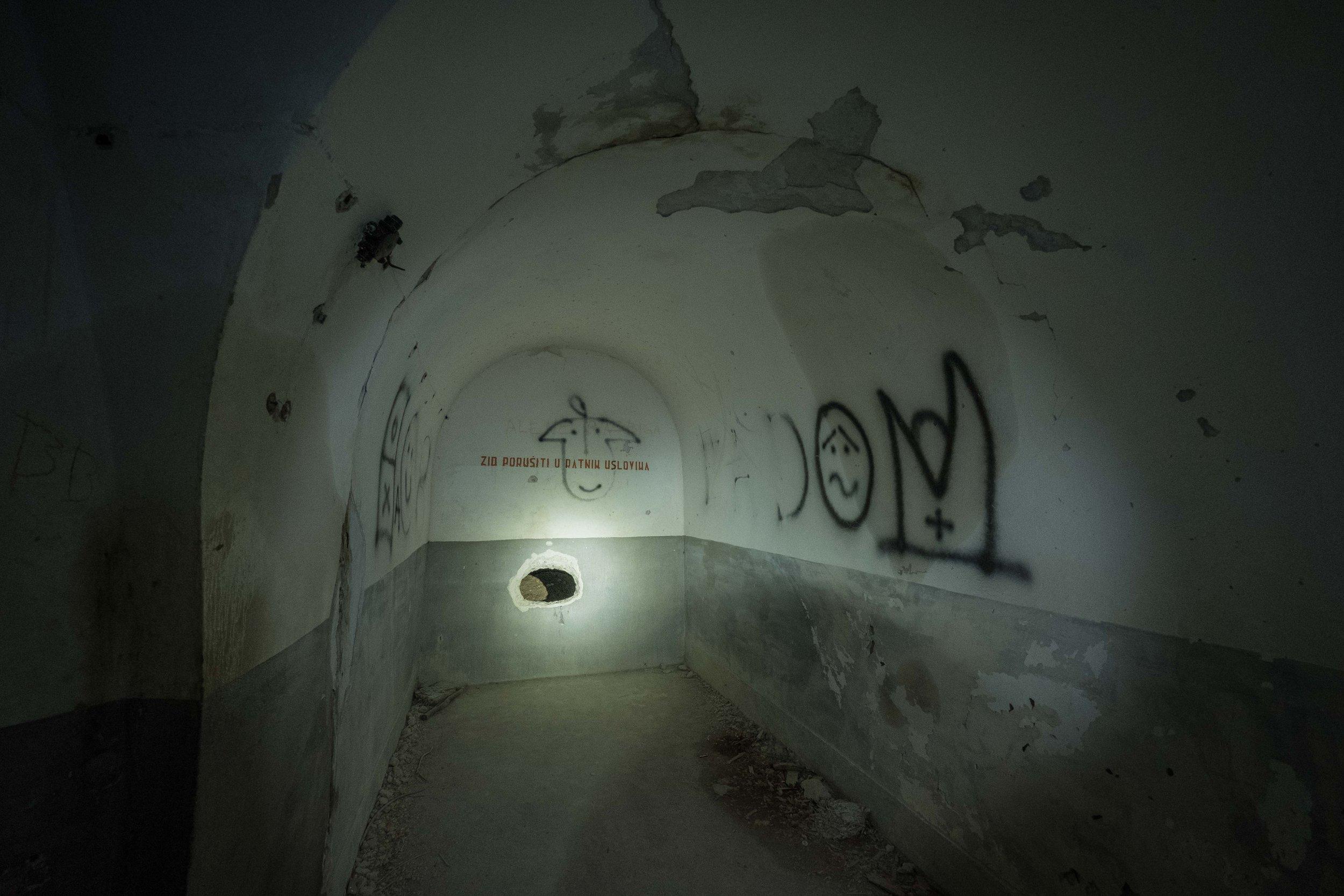 """zid porušiti u ratnim uslovima"" or, roughly translated, ""break wall in case of war""; behind the plaster was a crude tunnel out"