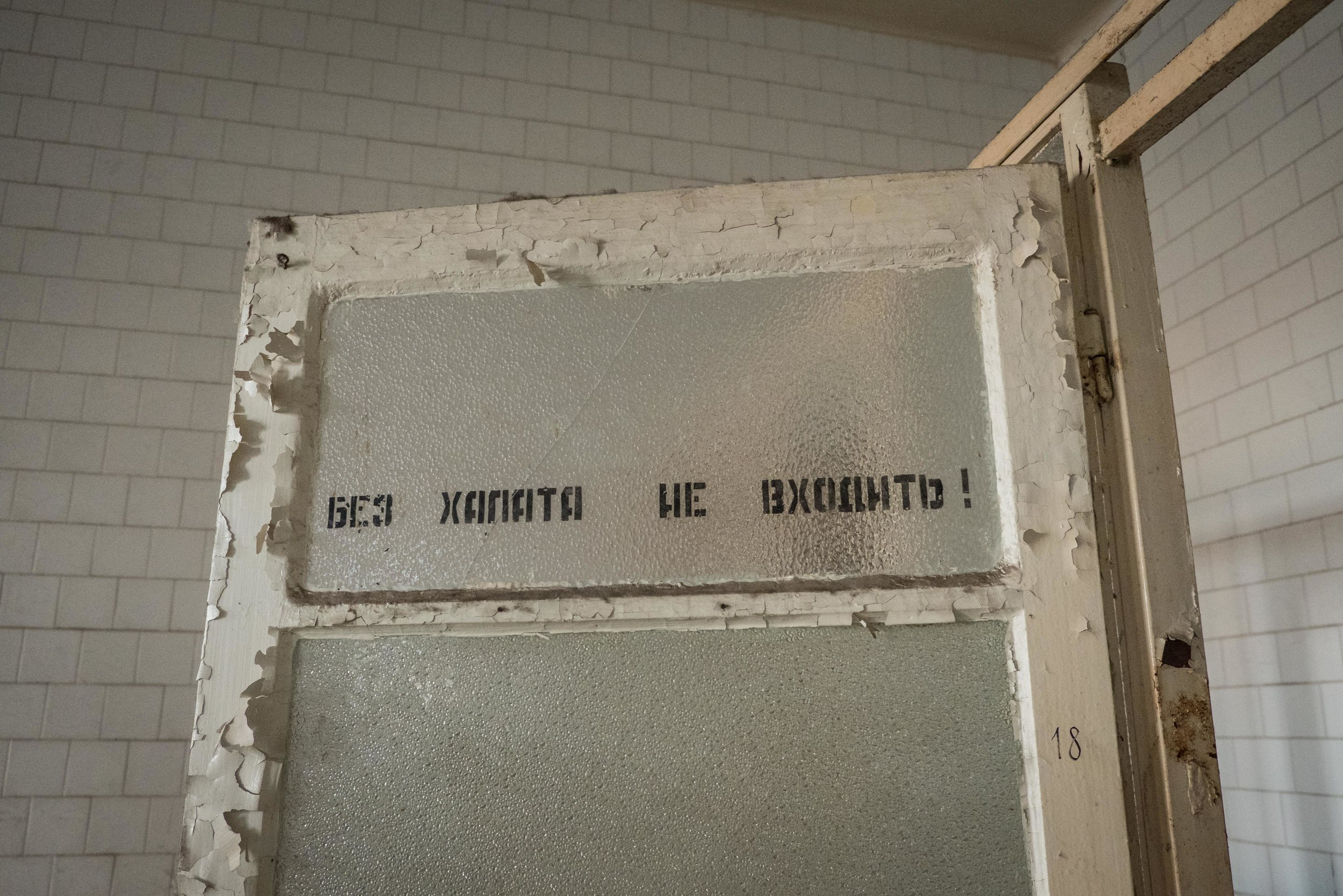 a stern reminder in Russian about wearing a doctor's coat