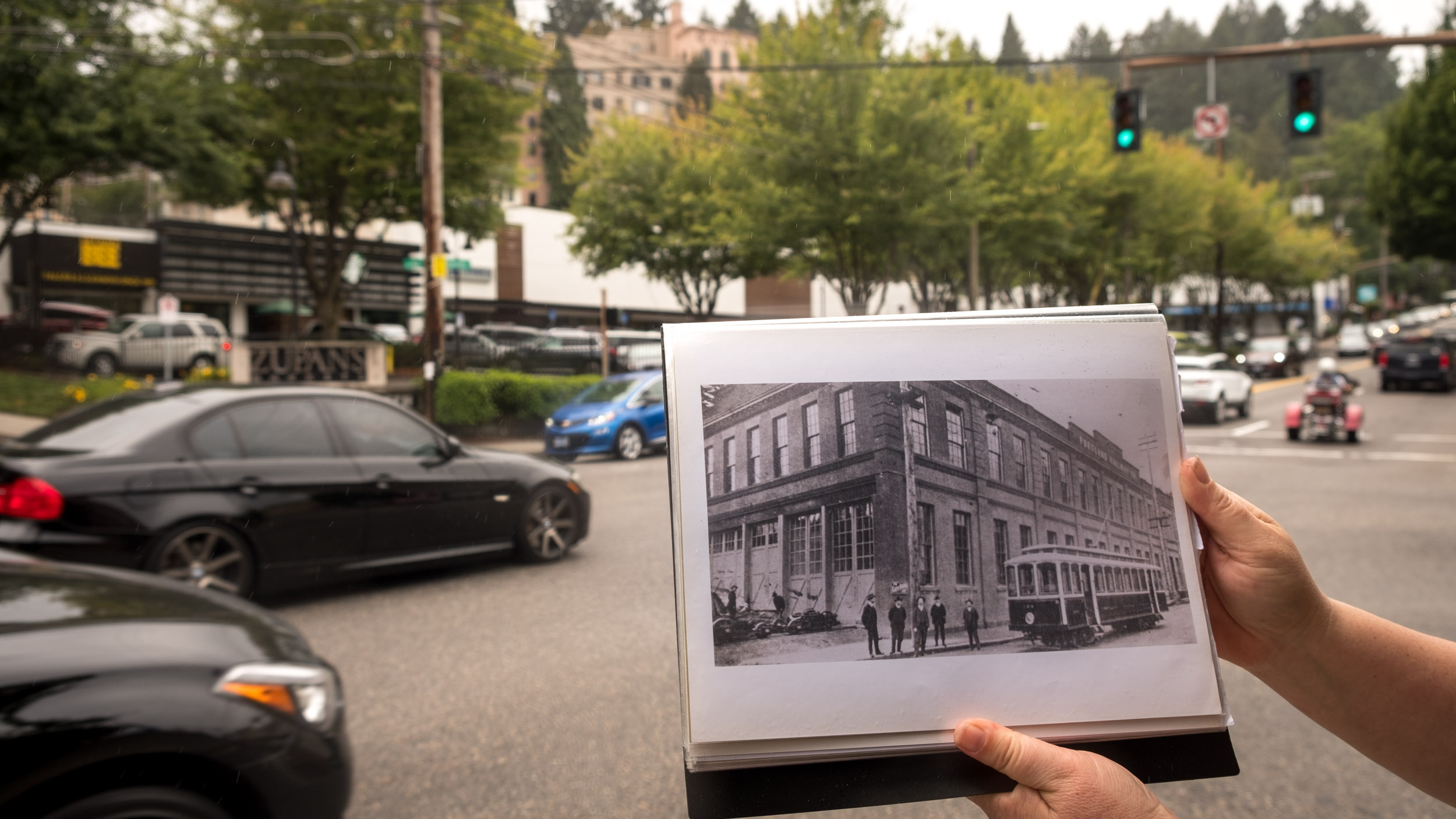 Tanya of Slabtown Tours holds up a historic photo of the building and trolley at 23rd and Burnside removed to accommodate cars