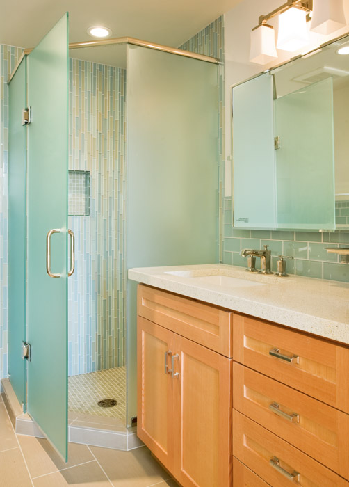 Glass tile with Douglas Fir cabinets complementthe light airy feel of the second bath.  Heavy glass doors complete the angled shower with vertical tile installation for a reed like feel.