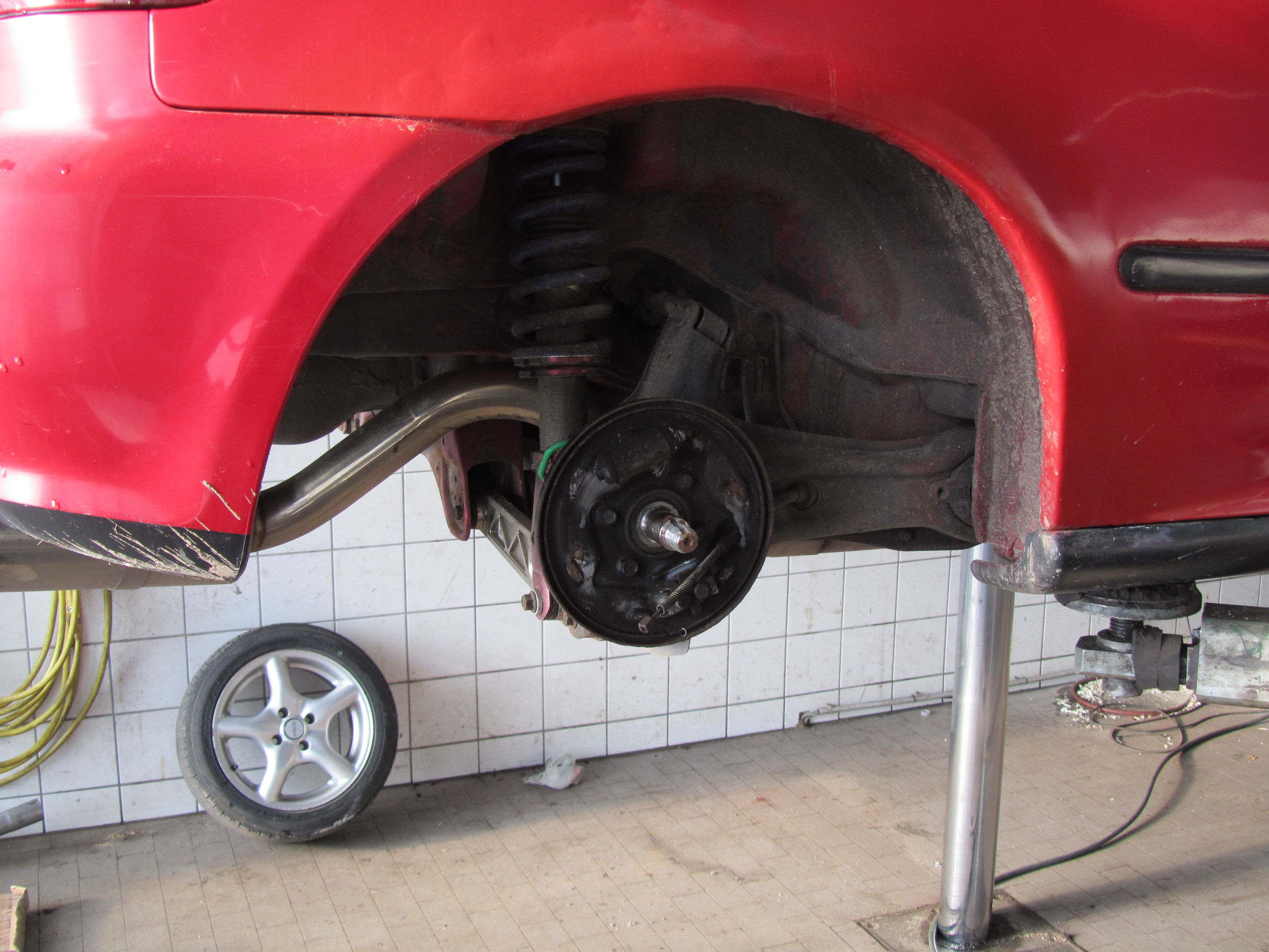 """1. Arriving at the garage shortly after 8 am, I put the car up in the air and together with one of the mechanics, we set out to """"crack"""" the drum brakes open to remove them and disconnect the handbrake cable."""