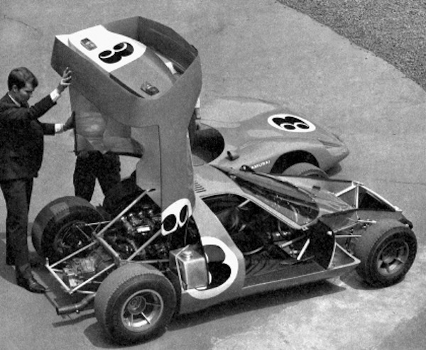 """Pete Brock demonstrating the large """"clam shell"""" engine cover."""