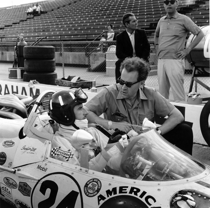 Eric Broadley and Graham Hill sharing a moment in the pits.
