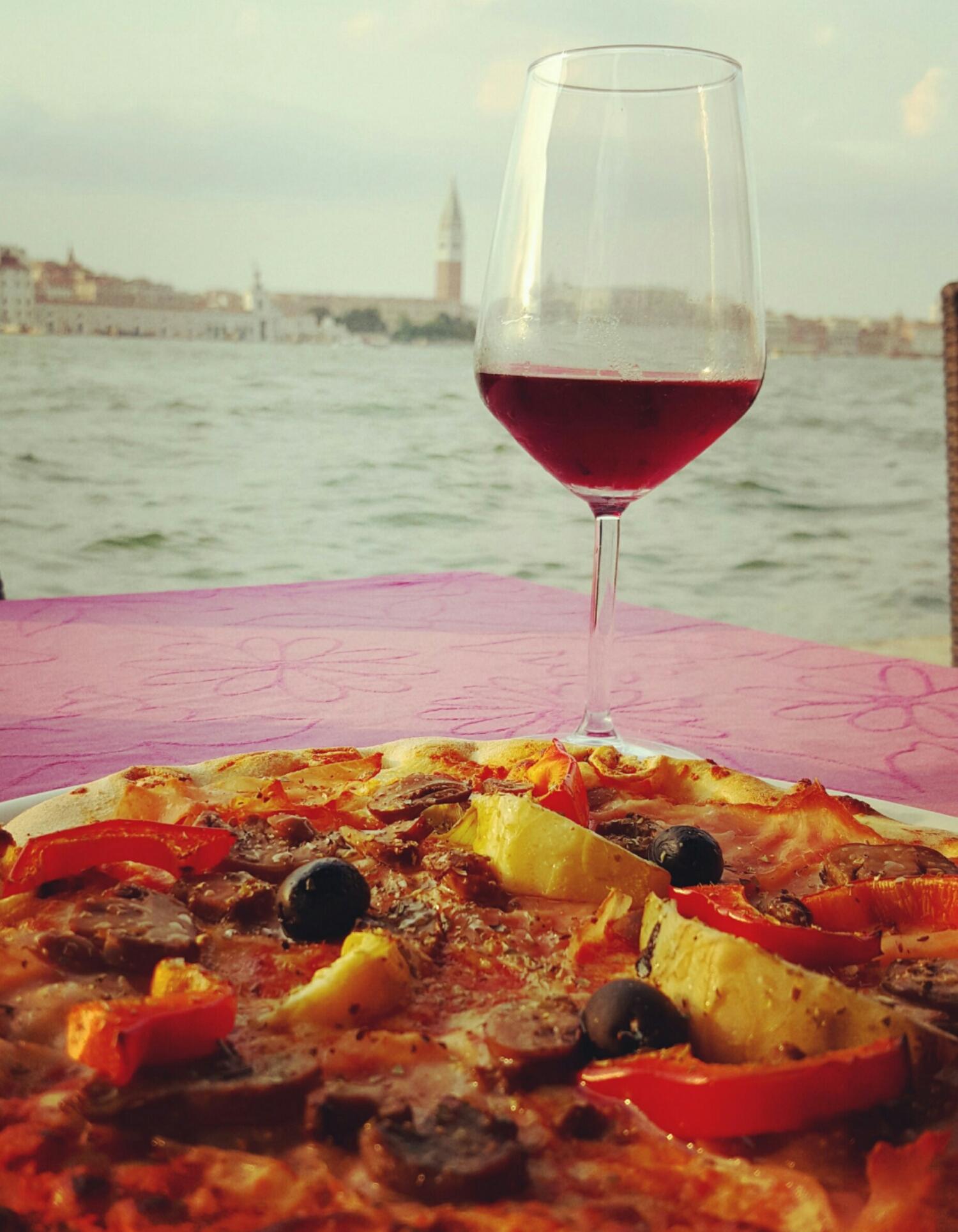Pizza y vino italiano con atardecer en Venecia