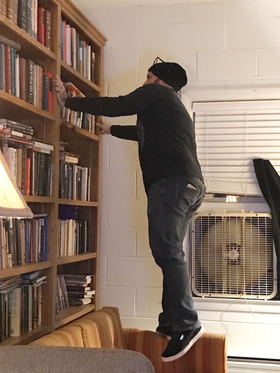 Joe can't reach half of the books on his shelves without standing on his couch.