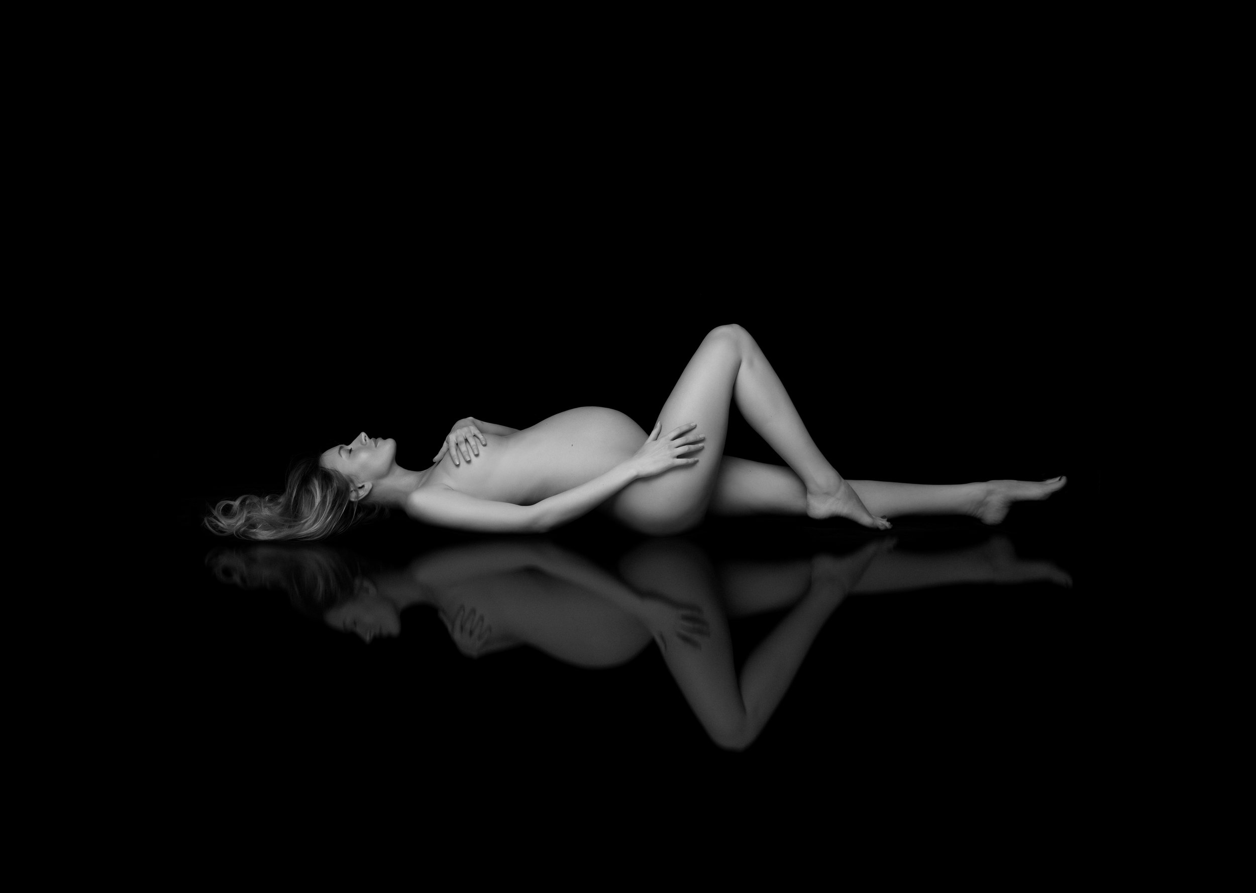 beautiful pregnant woman laying down on black floor, photo studio New York