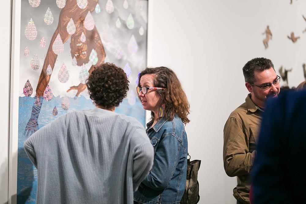 Women looking at and discussing Katrina Andry print