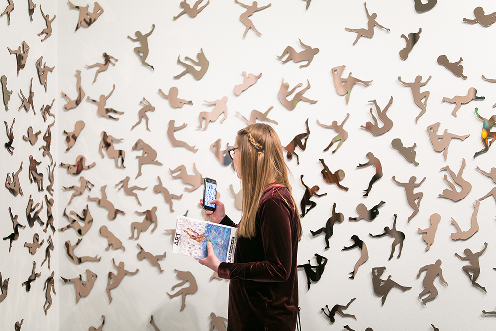 Woman taking photo with iPhone of Katrina Andry installation