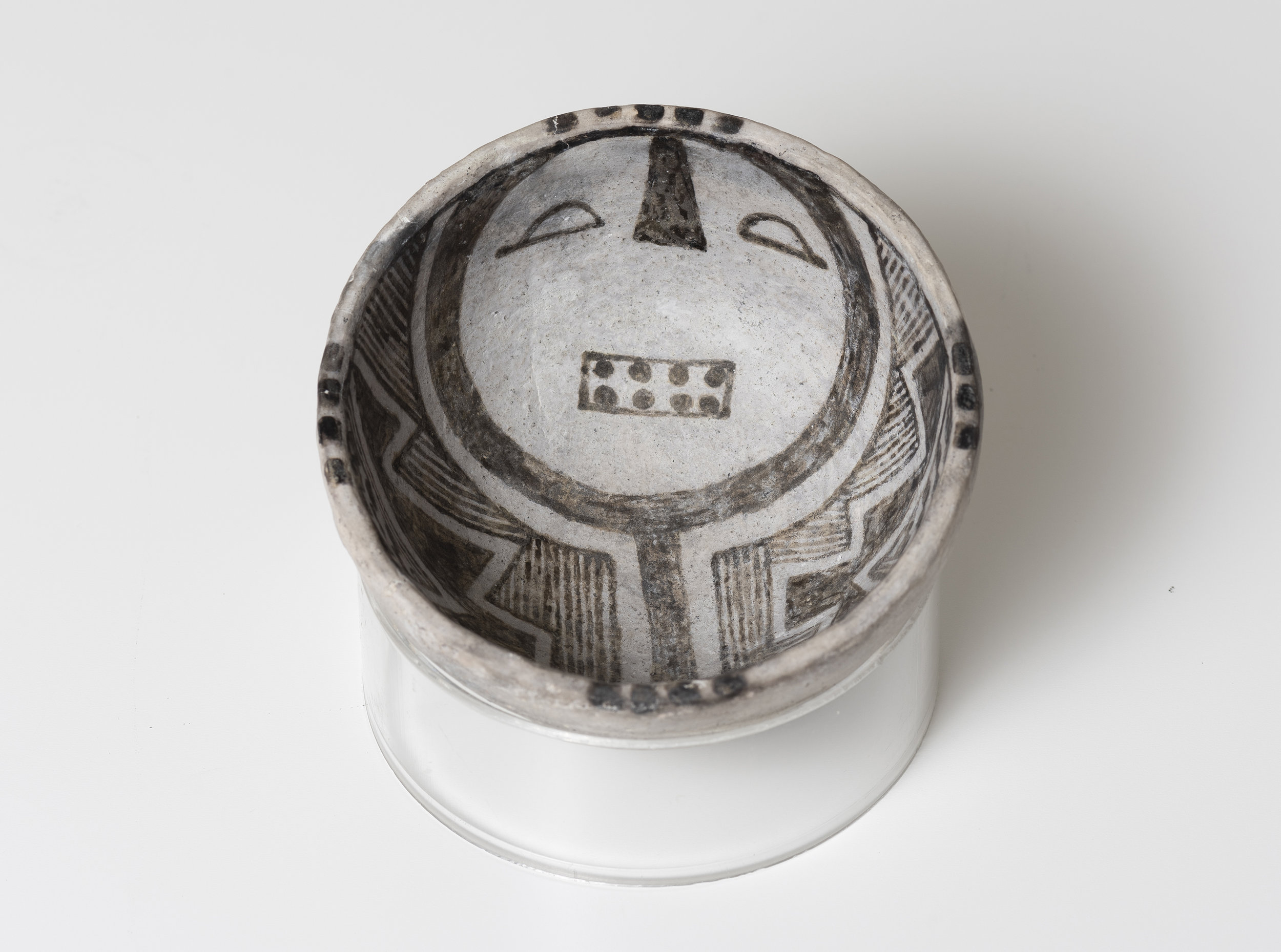 Snowflake Black-on-White  Humanoid face   c. 1175 - 1325 CE Painted ceramic 3.75 inches diameter, 2 inches depth