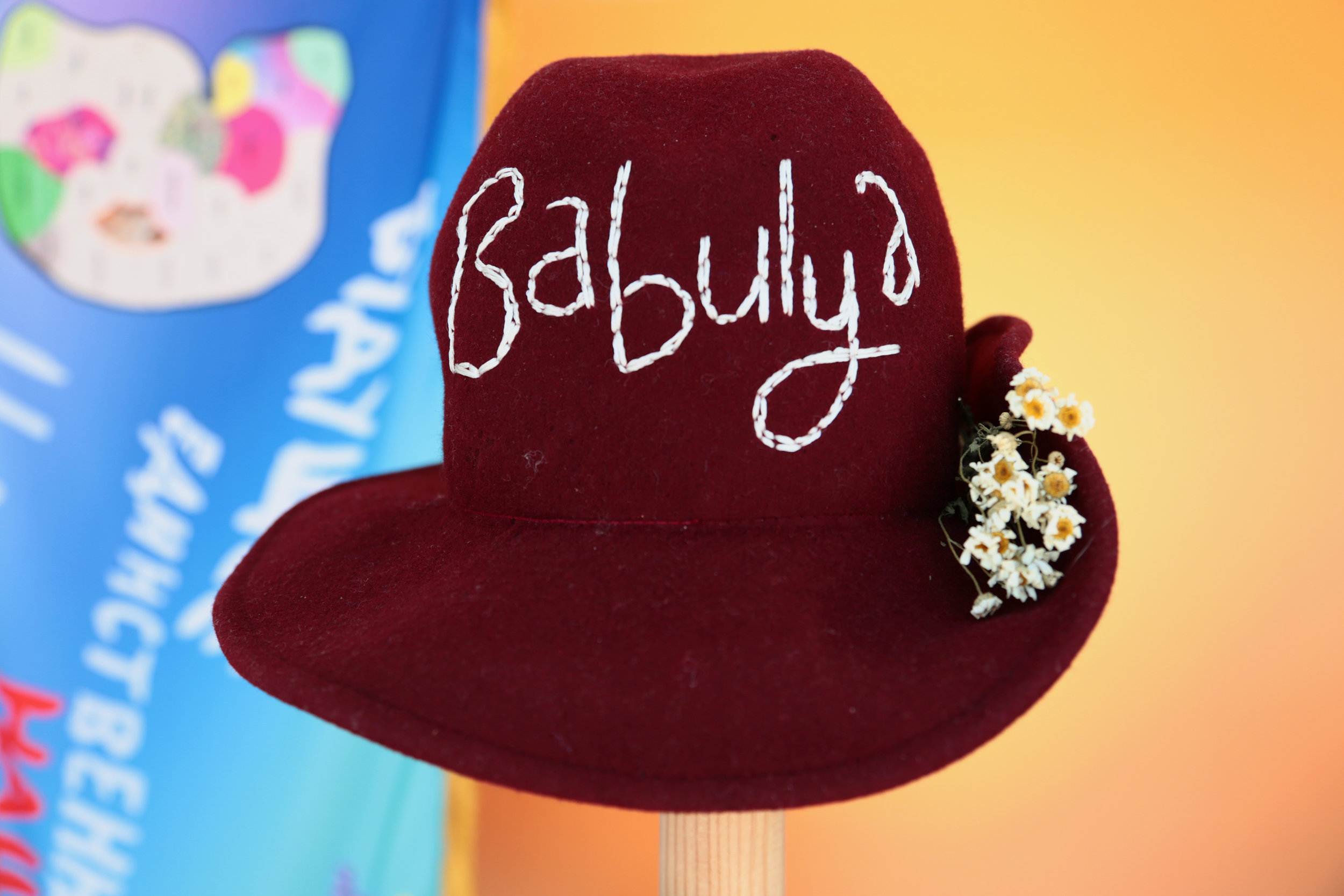 Molly Surazhsky бабуля  (Babulya)  detail    2019   Printed satin, canvas, tulle, wool hat, sherpa fleece, gold candles, embroidery floss, chrysanthemum
