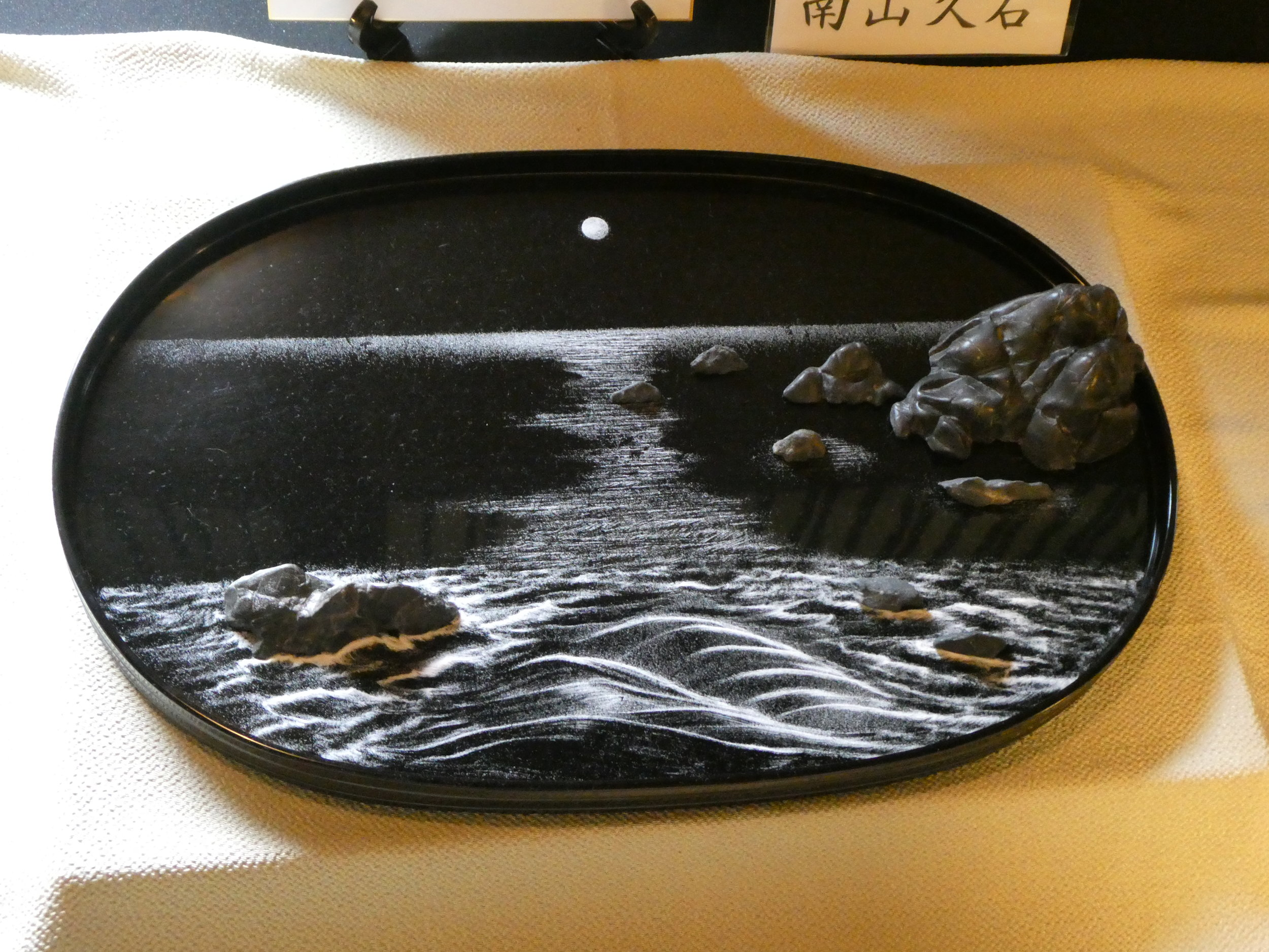 An example of Bonseki, the ancient Japanese art of creating miniature landscapes on black lacquer trays using only white sand, pebbles, and small rocks.