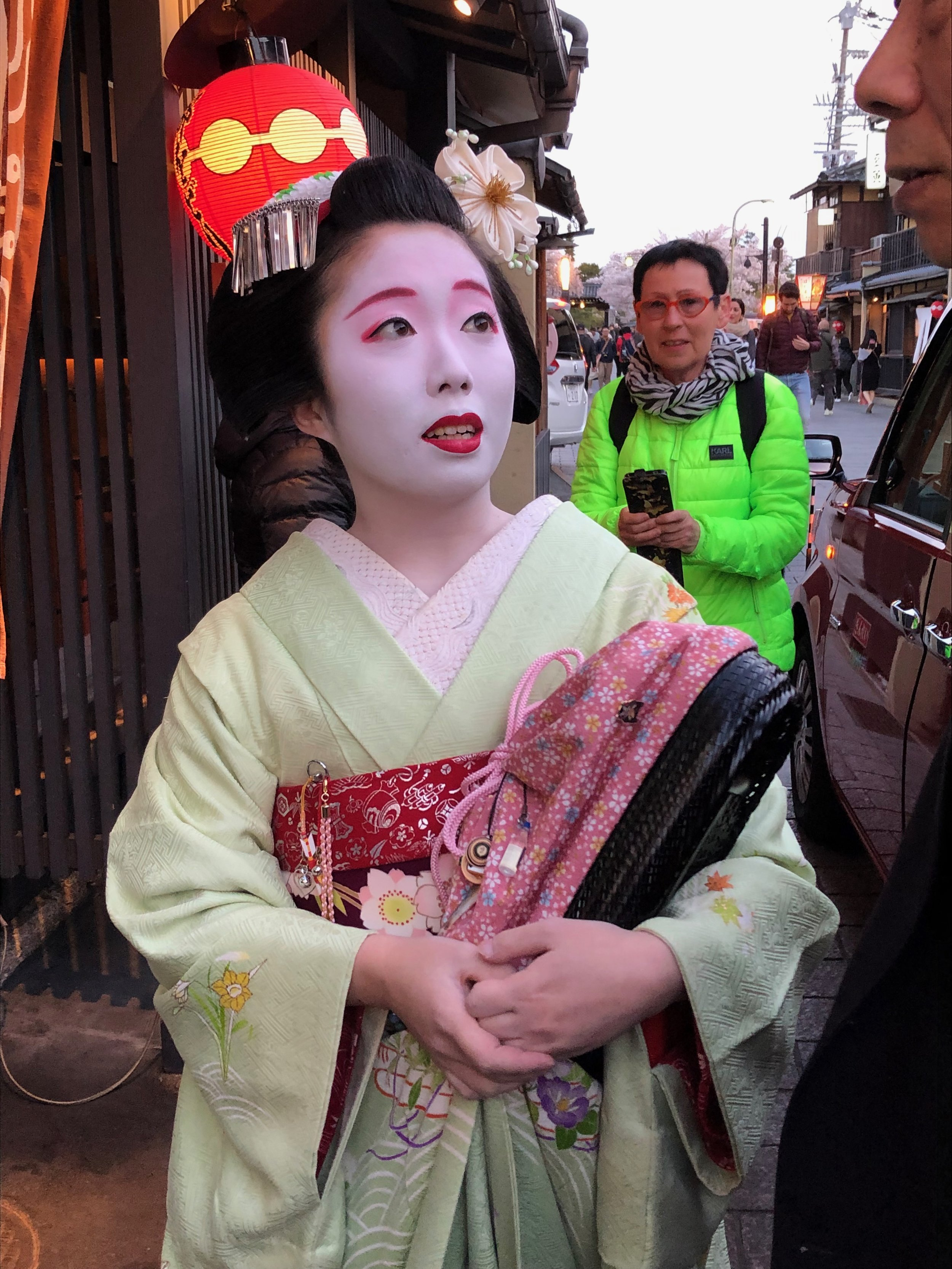 Distressed geisha surrounded by dozens of tourists snapping photos, seeks refuge in a limousine.