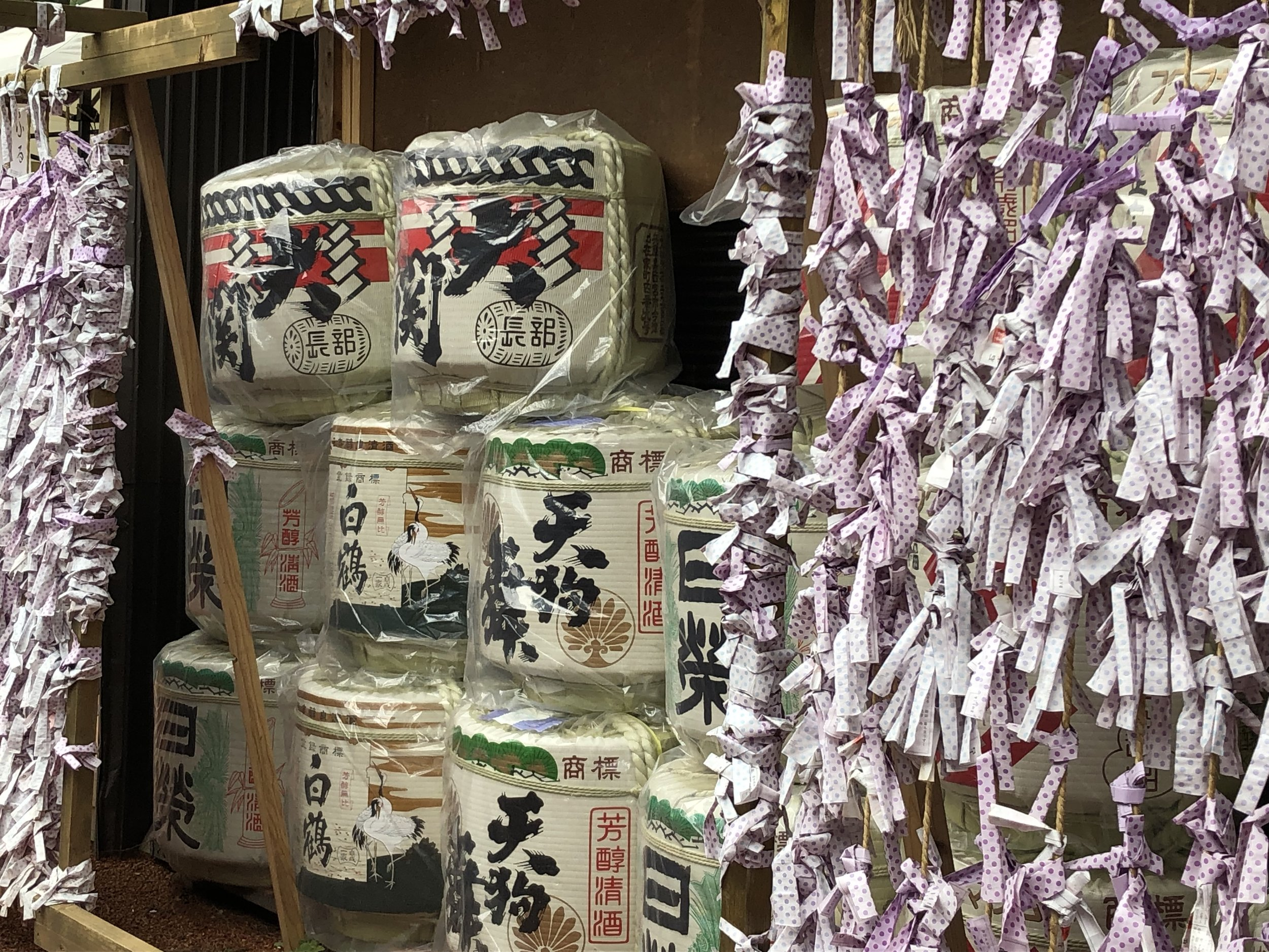 Outside the temple, thousands of wishes are tied to the fences which are interspersed with barrels of saki.