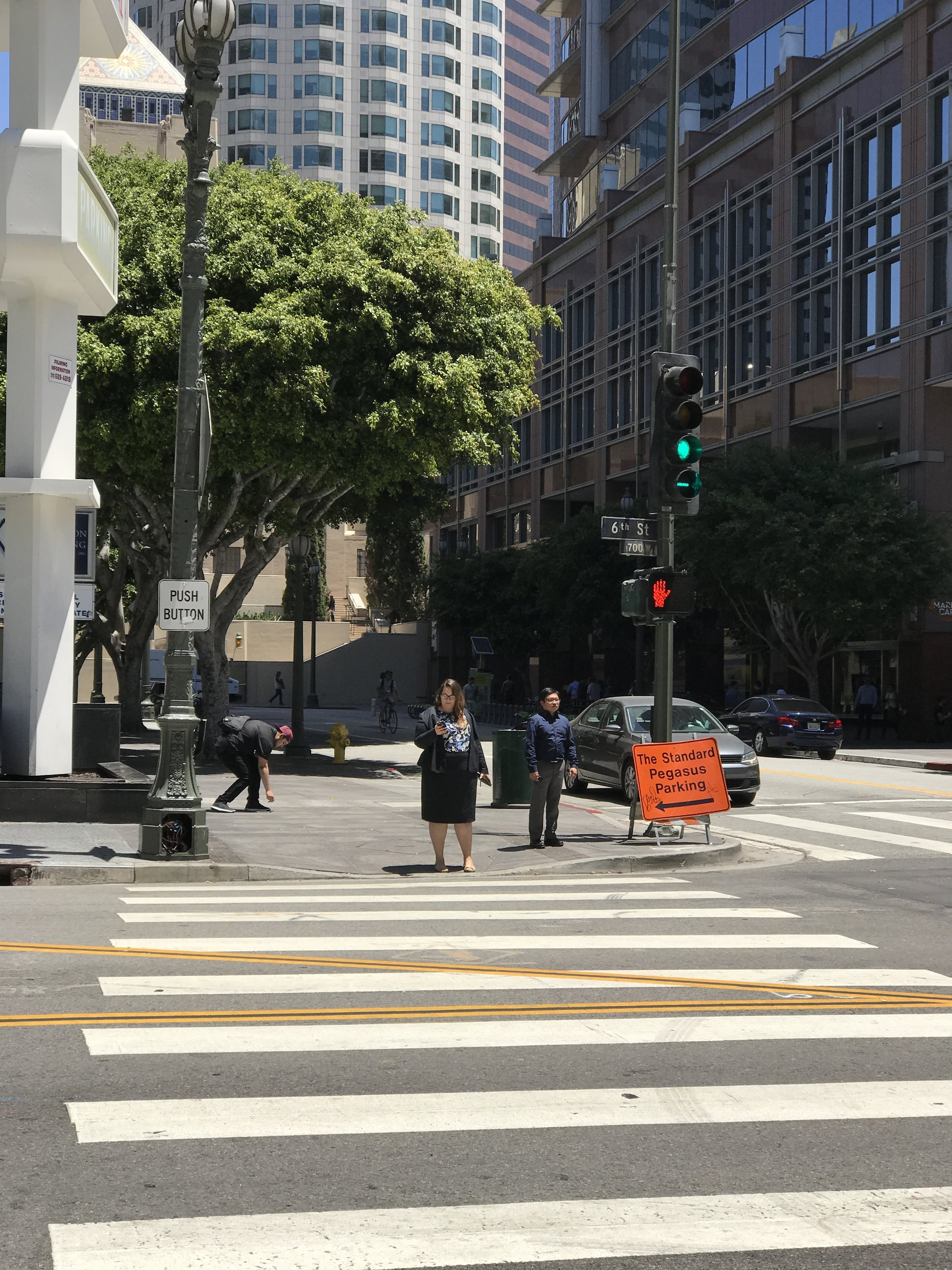 """The reengineered intersection of Hope and 6th Streets in Downtown Los Angeles, with signage commanding pedestrians to """"PRESS BUTTON"""" for permission to cross."""