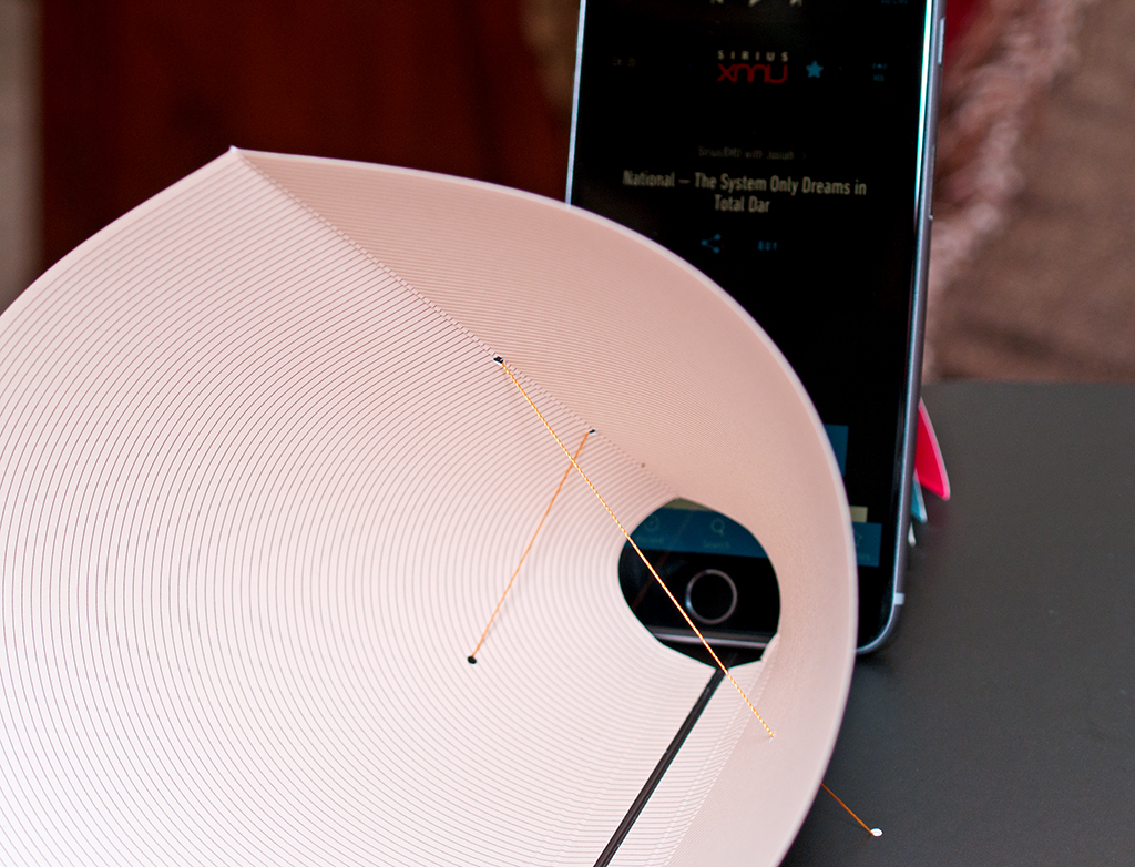 The pop up holds the cellphone at the cone, which amplifies the sound level of the playing music.