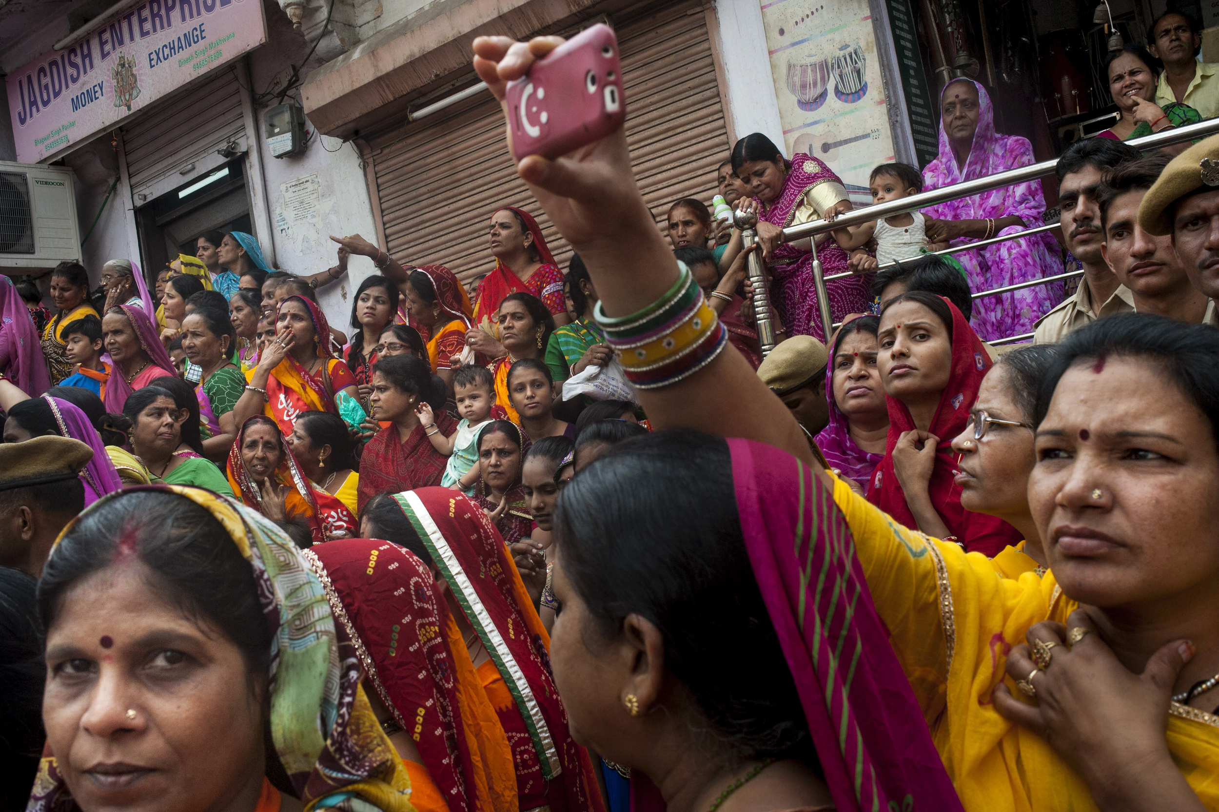 Women gather together in the back of the crowd behind male parade goers to watch the Krishna festival parade in Udaipur on July 17, 2015. Public space, by definition, are areas designated to be accessible to all individuals. However, separation of gender in space is seen throughout a historically patriarchal urban and rural Northern India, forcing women to seek out and create space for future generations of Indian women.