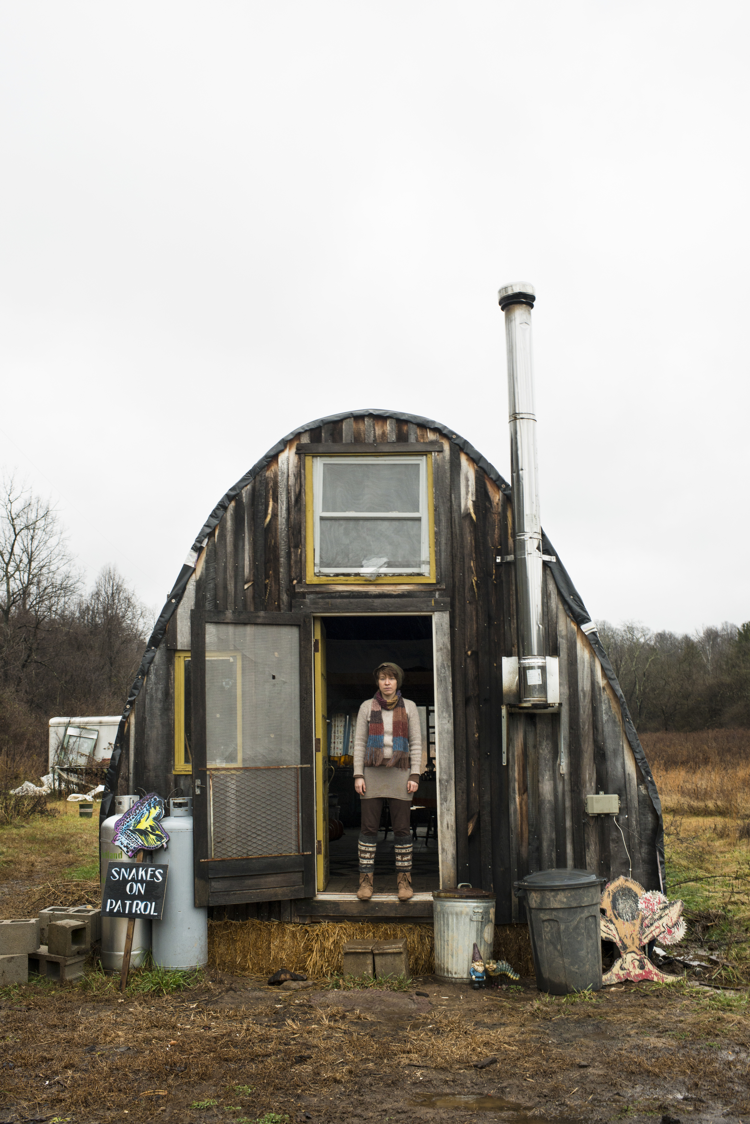 "Sarah Fick poses for a portrait outside of her off-the-grid wigwam in Rutland, Ohio that she built in order to be closer to the land and escape the commodities of everyday life. ""It was just this constant yearning to live more closely to the earth and to not be hurting the world,"" said Sarah."