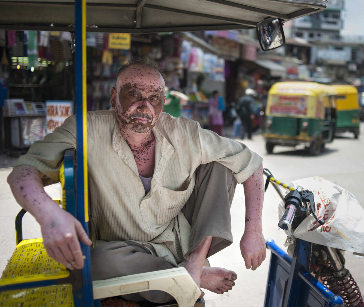 A rickshaw driver poses for a portrait between taking customers in the Main Bazaar of Paharganj in New Delhi on July 13, 2015.