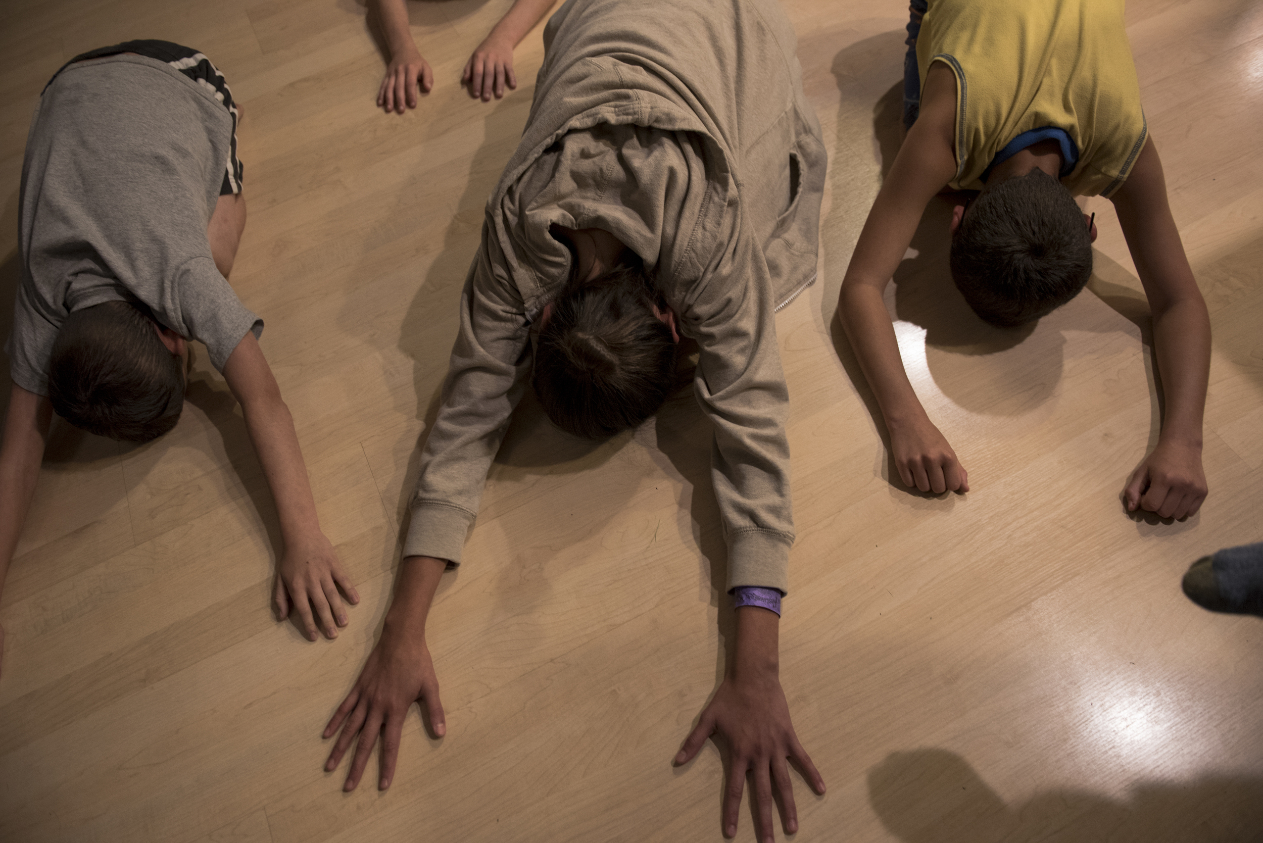 "From left to right, Liam, Olivia, and Sean practice yoga with their mother in their living room. DJ teaches her children many different practices for healing, such as yoga and trauma release exercise (TRE). ""How can I help these kids overcome and push through and grow into functioning human beings at their healthiest? What tools can I give them?"""