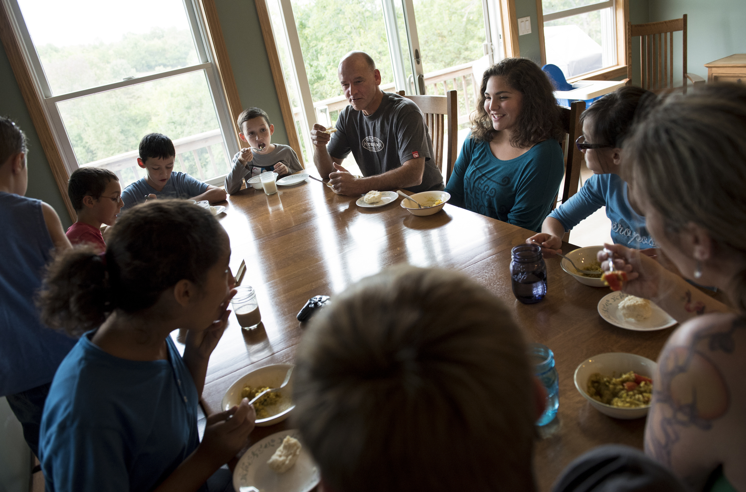 The Fullers sit down to dinner at their home in Athens, Ohio, where they moved from there home state of Oregon to start fresh for their eight children, seven of whom are adopted.