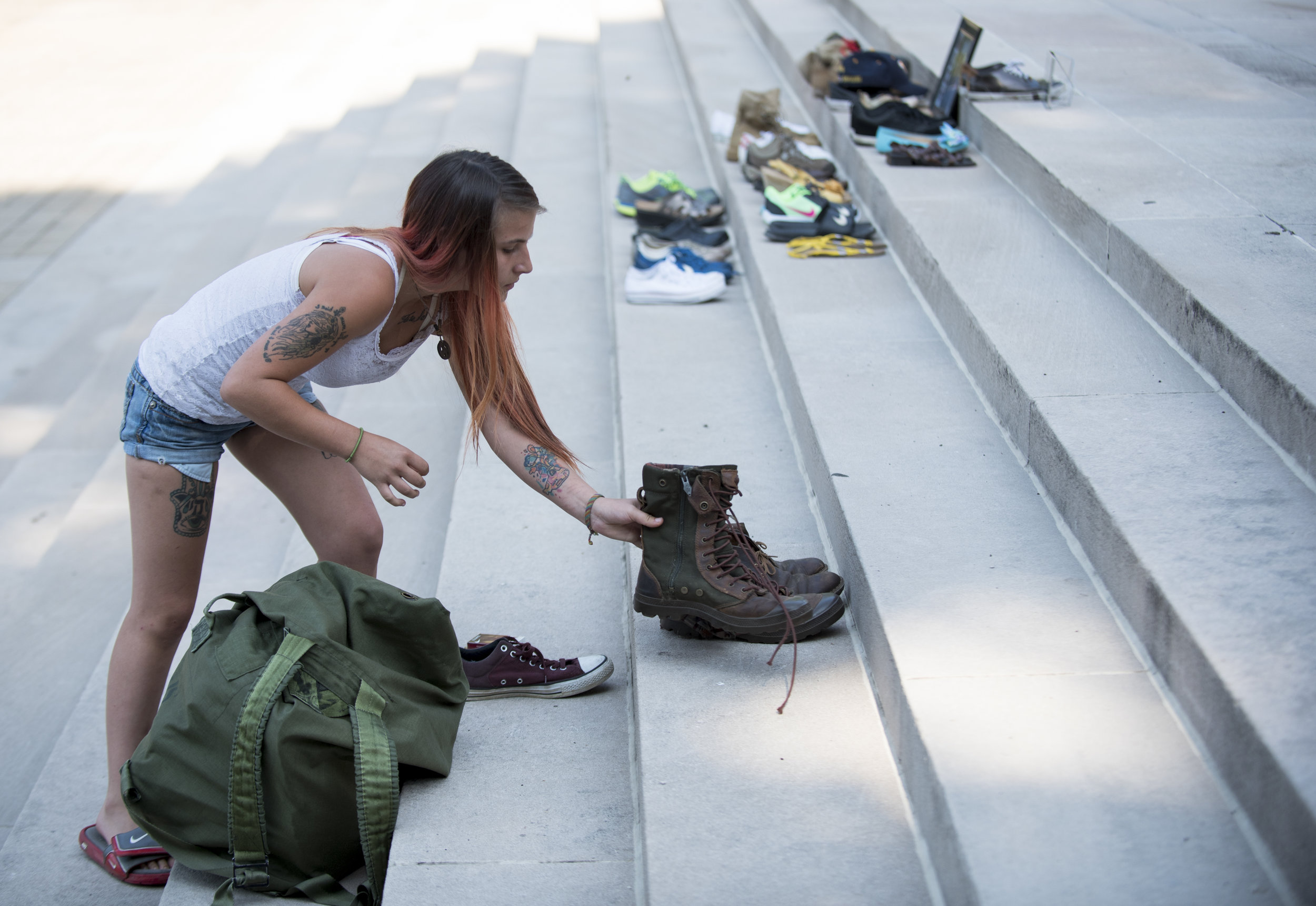 """PK Tyler brought a duffle bag filled with pairs of shoes to commemorate those she knew who were lost to drug overdose. """"There should've been a lot more [shoes],"""" said Tyler, who says she can't remember everyone she's lost to an overdose."""