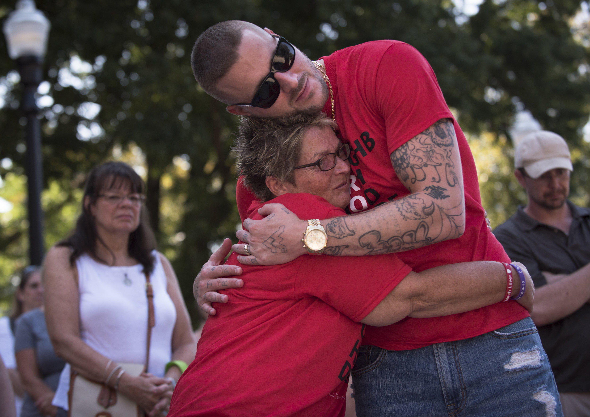"""Justin Ponton embraces Sue Ellen Chapman after she spoke of her late son Andrew Harrison Hutchison """"Hutch The Dutch"""" in front of a crowd of hundreds at the West Virginia Overdose Awareness Day Tribute at the State Capitol in Charleston, WV on August 27, 2016. Ponton is the director of the 9th Avenue Newness of Life recovery lifehouse."""